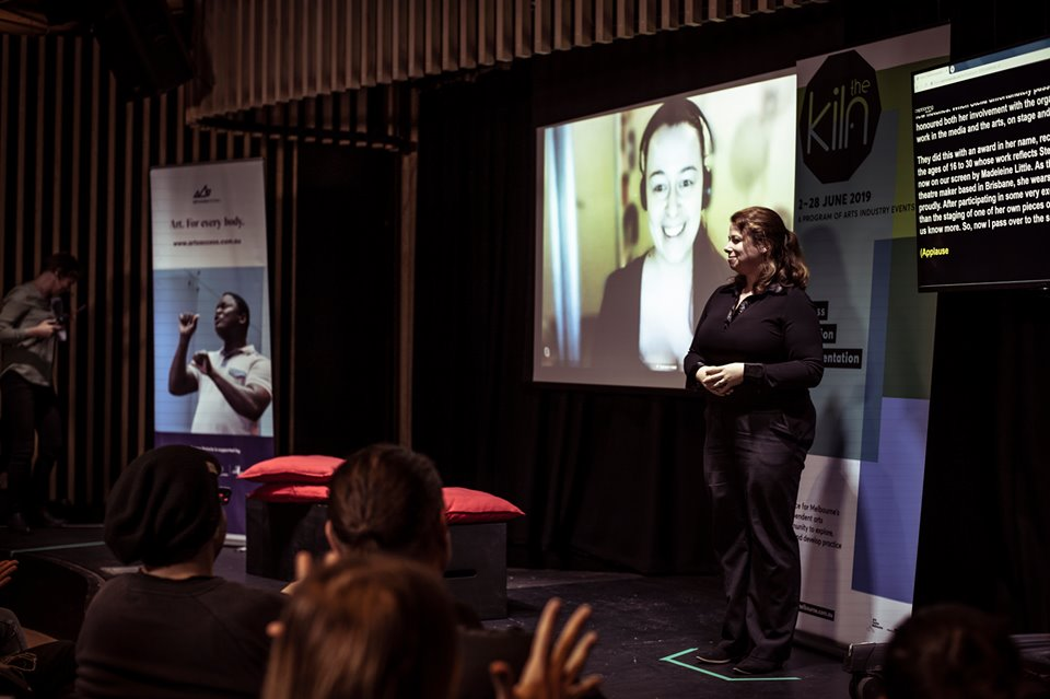 Advocacy - Image: Madeleine Little on the projector screen speaking via video conference at Arts Access Victoria's The Art of Pride Disabled & Deaf Artist Networking Event, 2019. In the foreground, an Auslan Interpreter stands. There is a screen with captions.