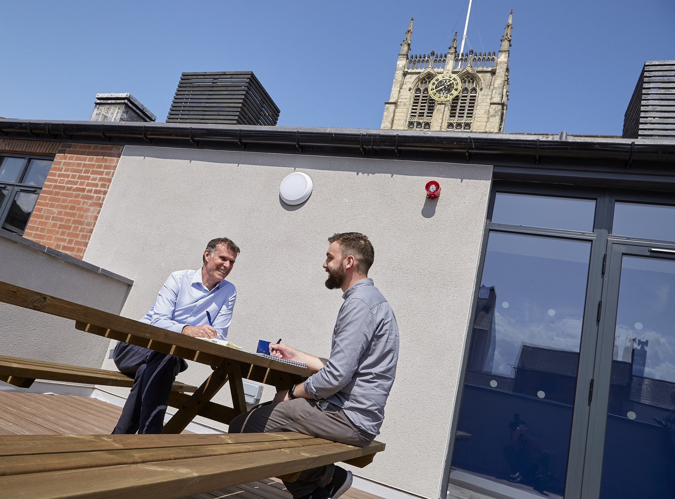 Project Manager Mark Bullivant, left, and Service Delivery Engineer Lewys Jones catch up on the roof terrace of APD's offices in the shadow Hull Minster.