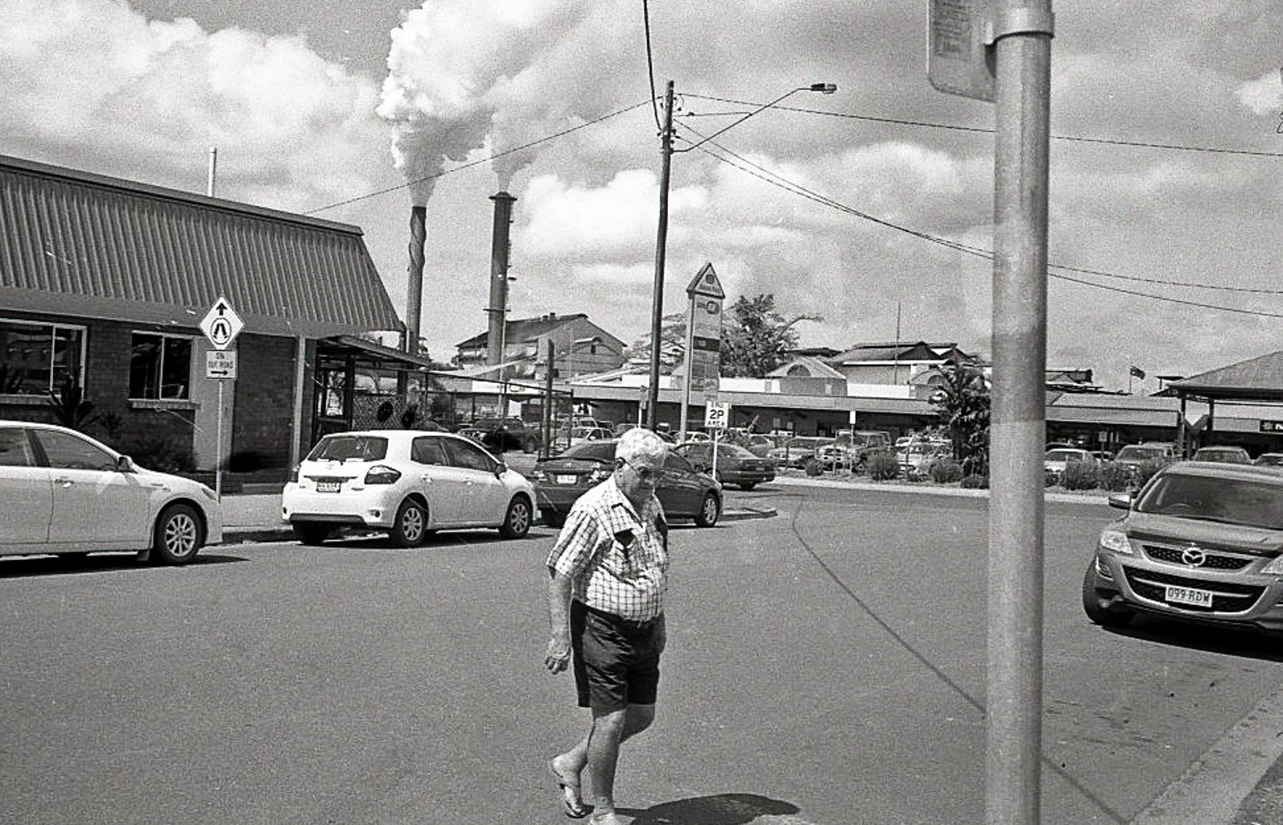 A older man crosses the road
