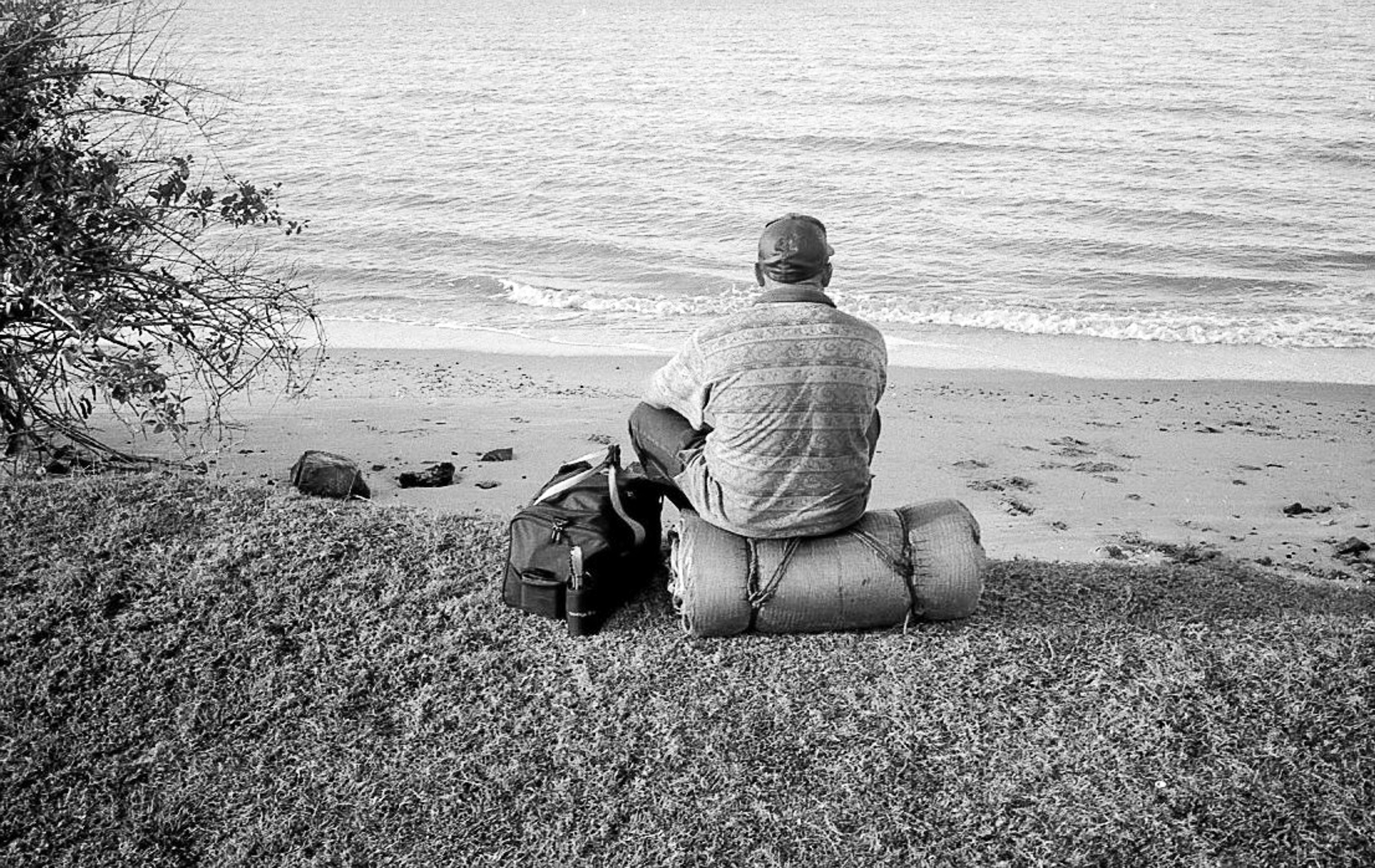 A man sits and looks at the occean.