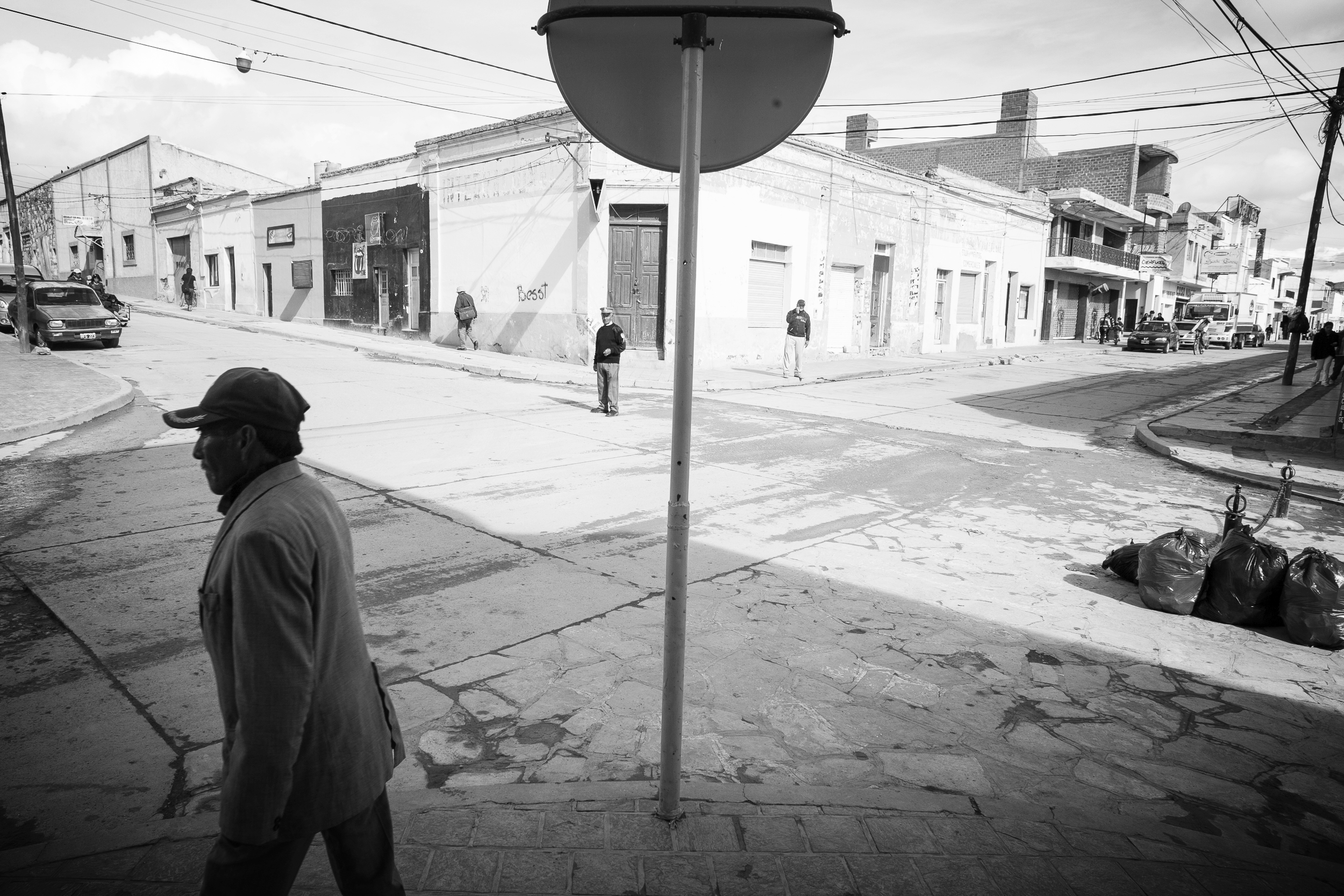 A man walks by as a police man keeps a look out. Boliva