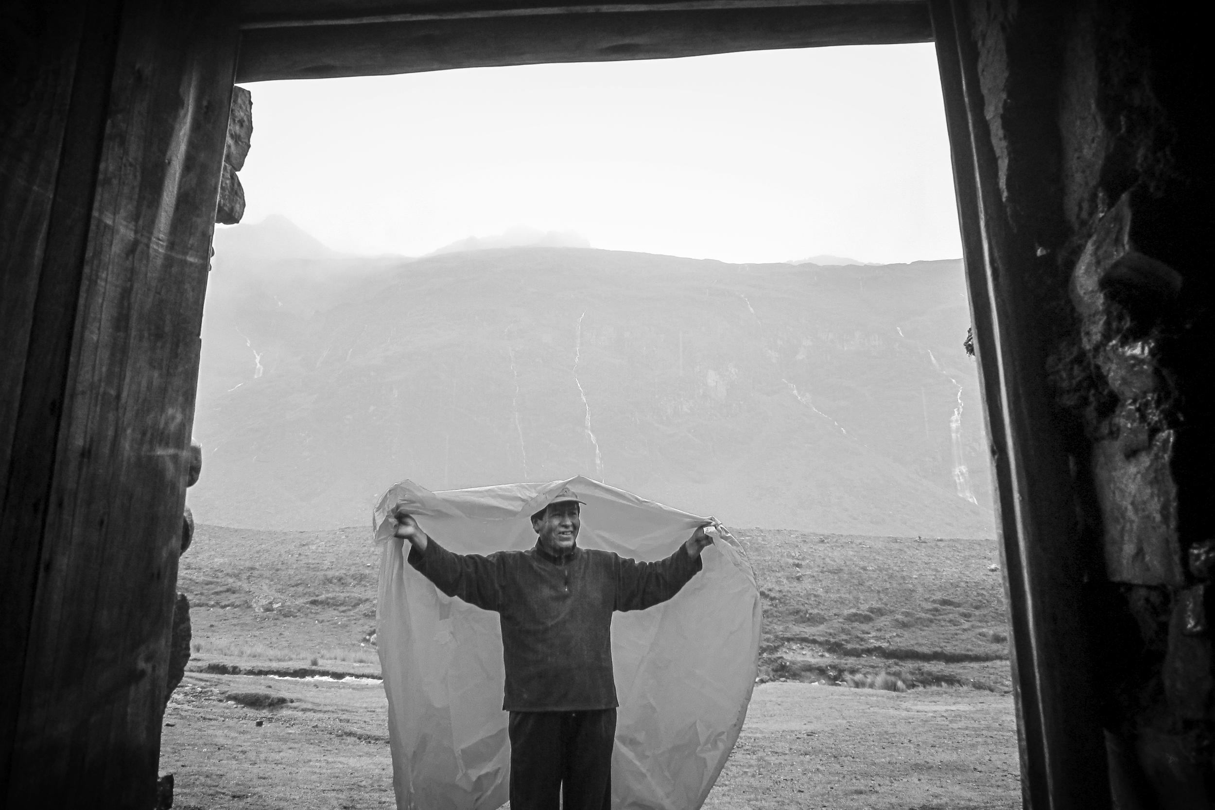 A bolivian man stands in the rain. Somewhere in Bolivia