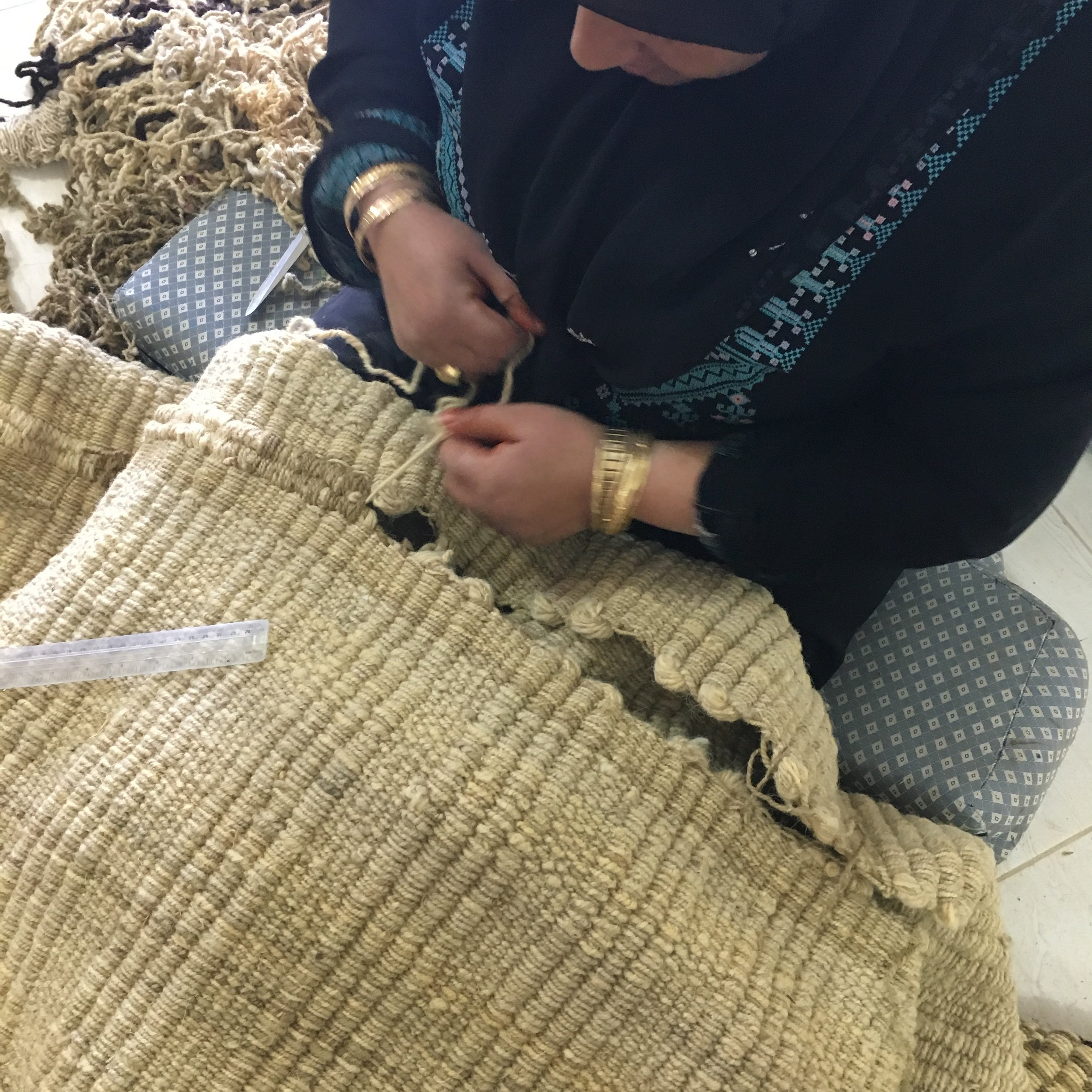 Siham is sewing two strips of women material together in a seam,