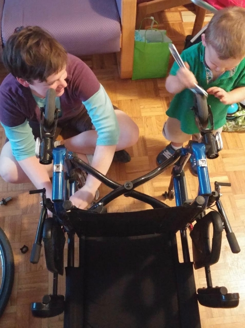 Marie and her son working on a friend's wheelchair.