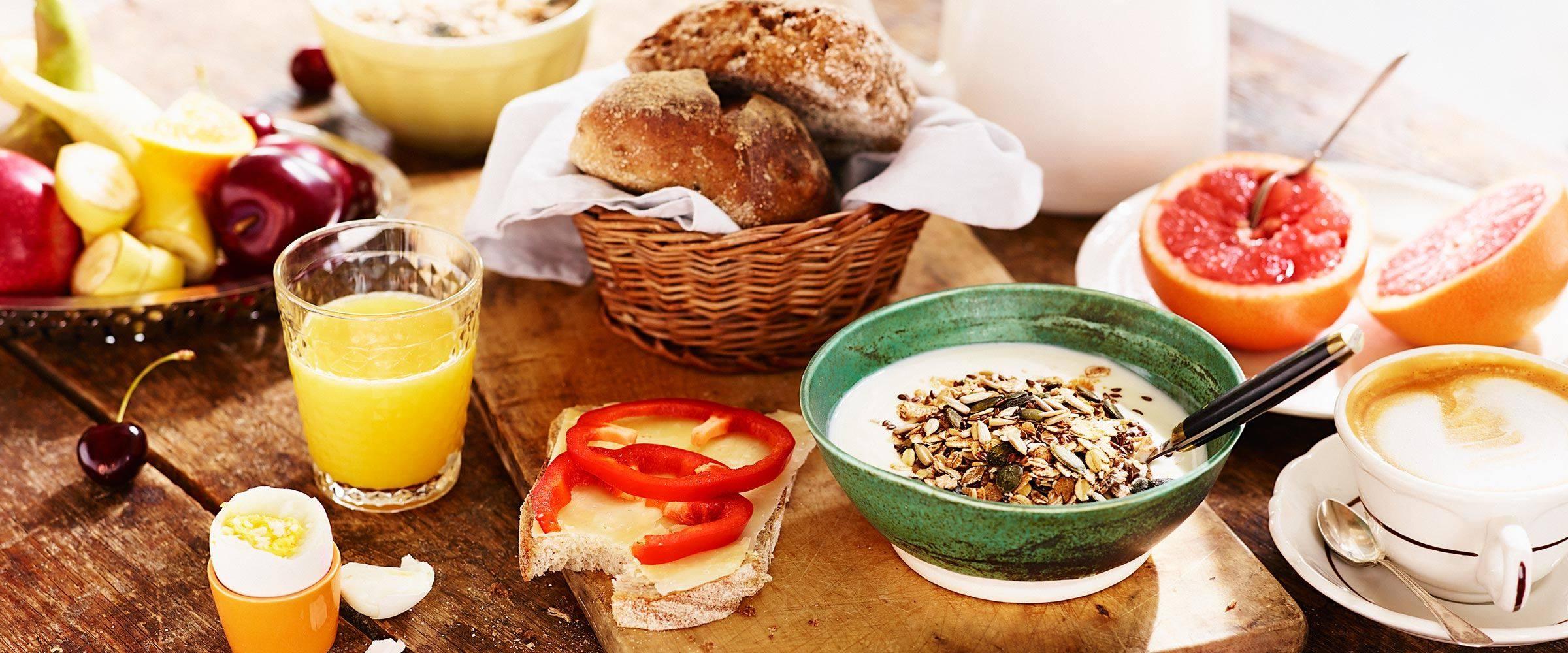 Uppdukad frukost med apelsinjuice, fil, frukt och smörgås.