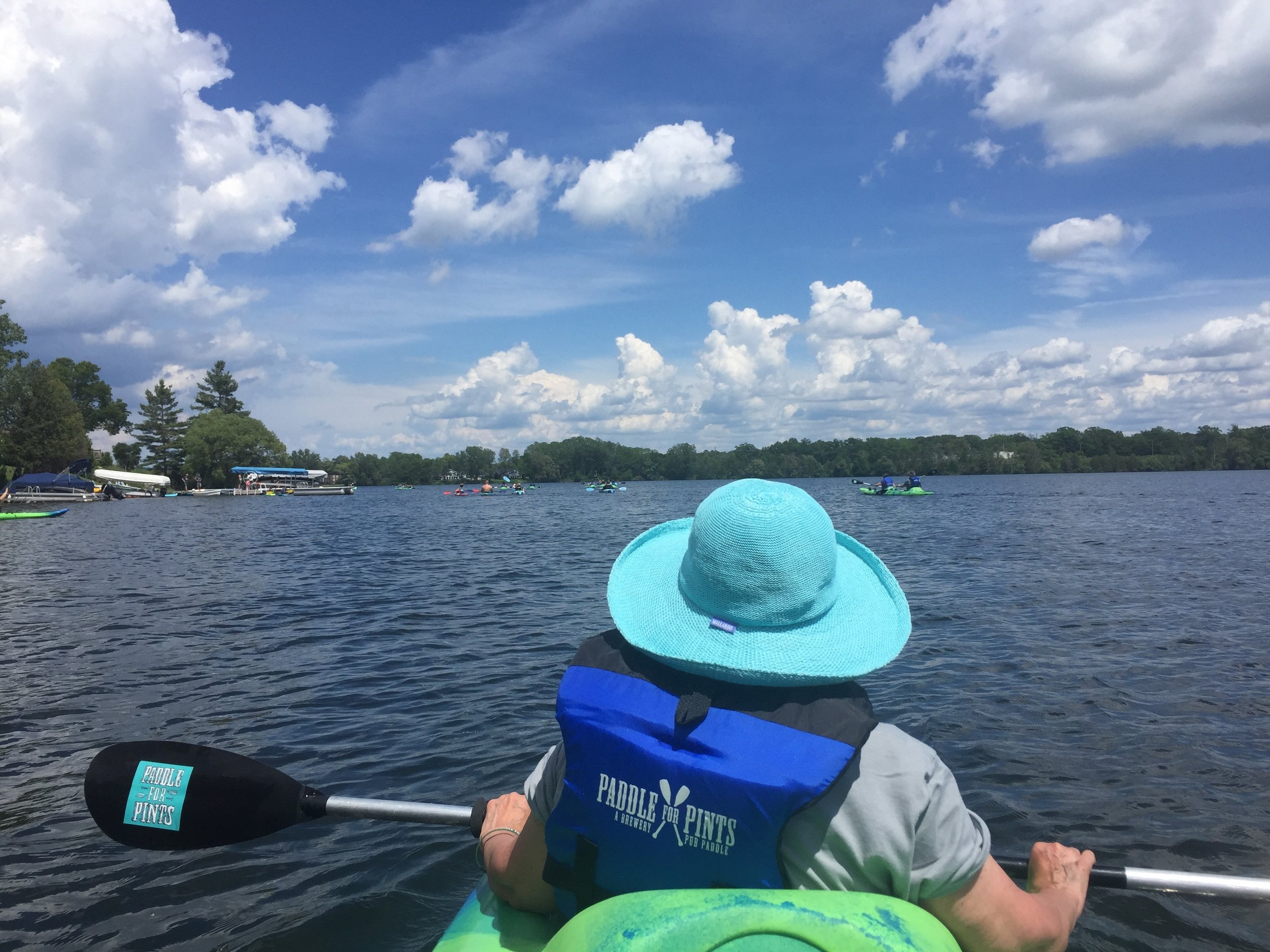 """The tour began on the Boardman Lake, where the group did the """"Paddle for Pints"""" on a sunny Friday afternoon. Paddlers experience different TC brew pubs via a water trail."""