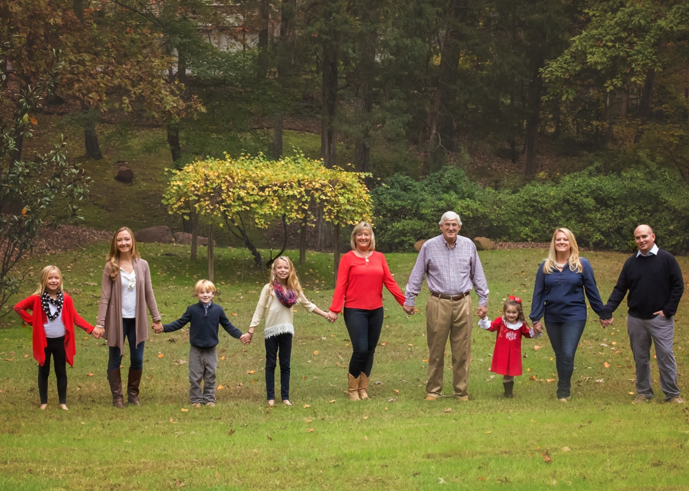 Family stands hand in hand for Sandford family photographer.