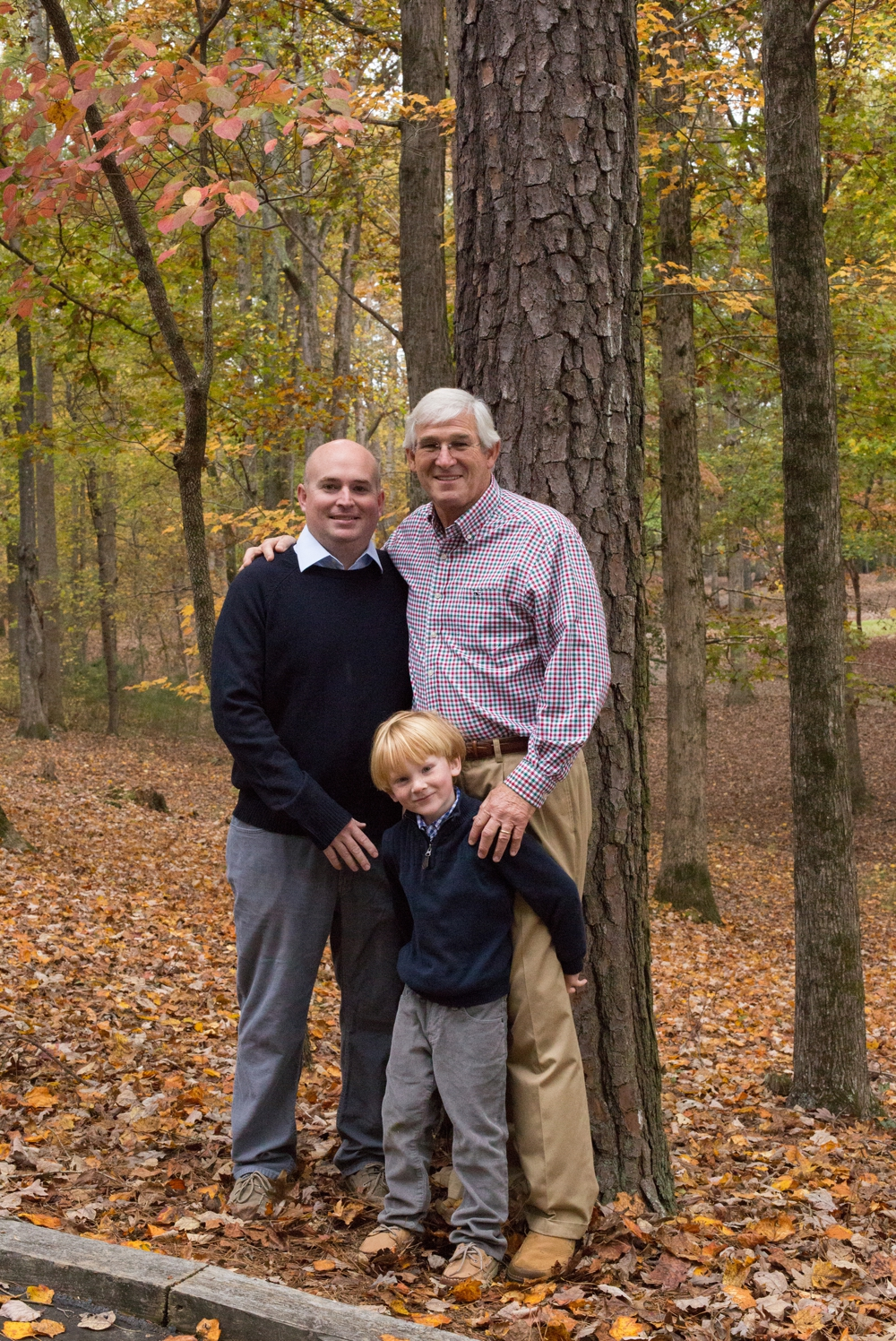 Dad and grandfather stand with boy for three generations photo.