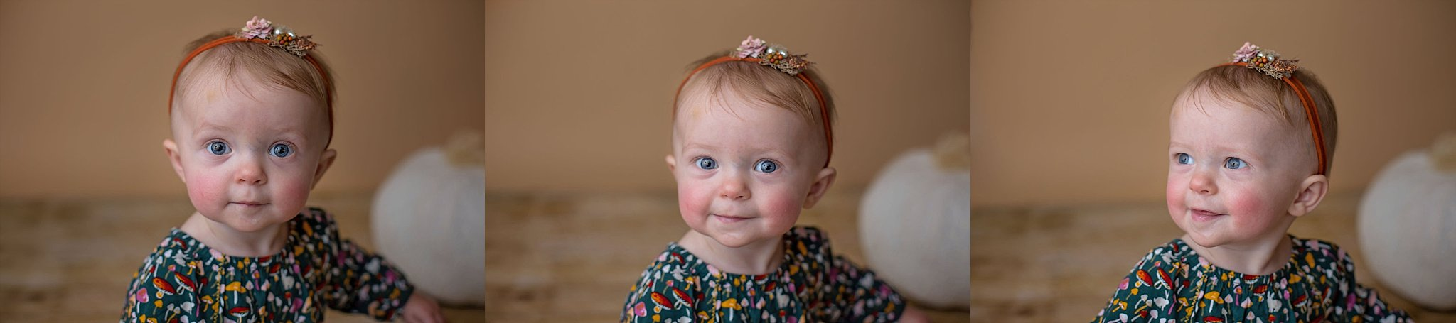 Baby girl smiles during one year birthday studio portrait session.