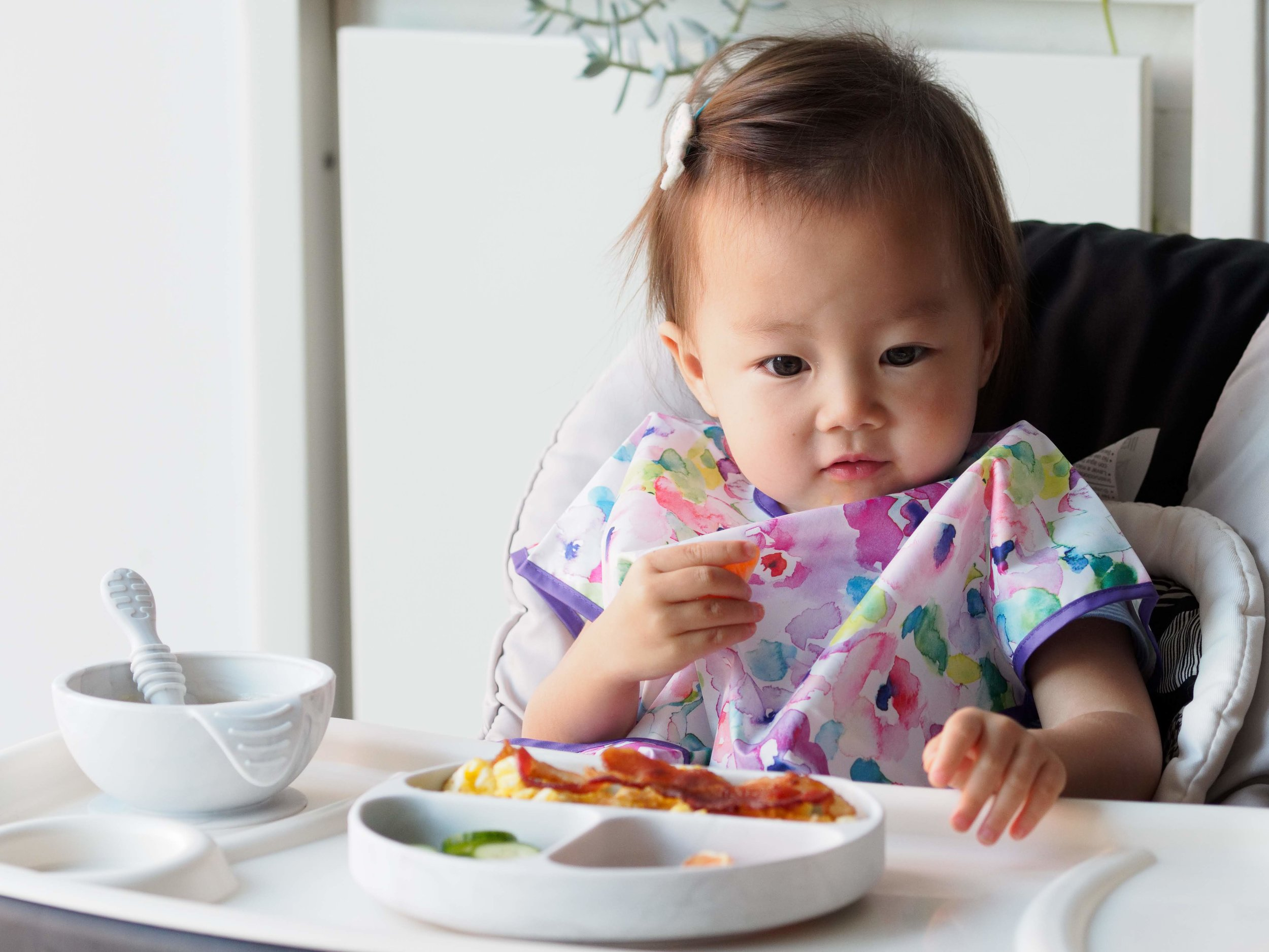 Jessica's daughter Max is pictured with Bumkins'    Junior Bib    in Watercolor,    Silicone First Feeding Set    in Marble, and    Silicone Grip Dish    in Marble.