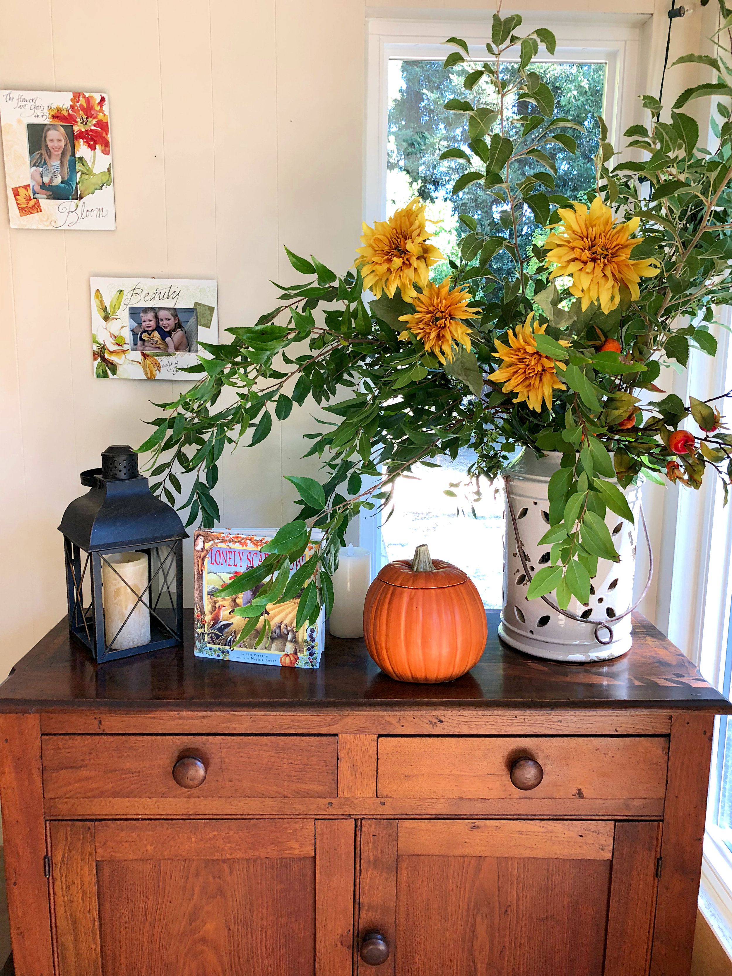 Fall decor - a mix of investments (the Pottery Barn candle, flower stems, and ceramic pot), Consignment finds (the buffet), Homegoods items (picture frames and lantern), hand-me-downs (my mom's ceramic pumpkin), a children's picture book, and nature (cut branches from our yard)