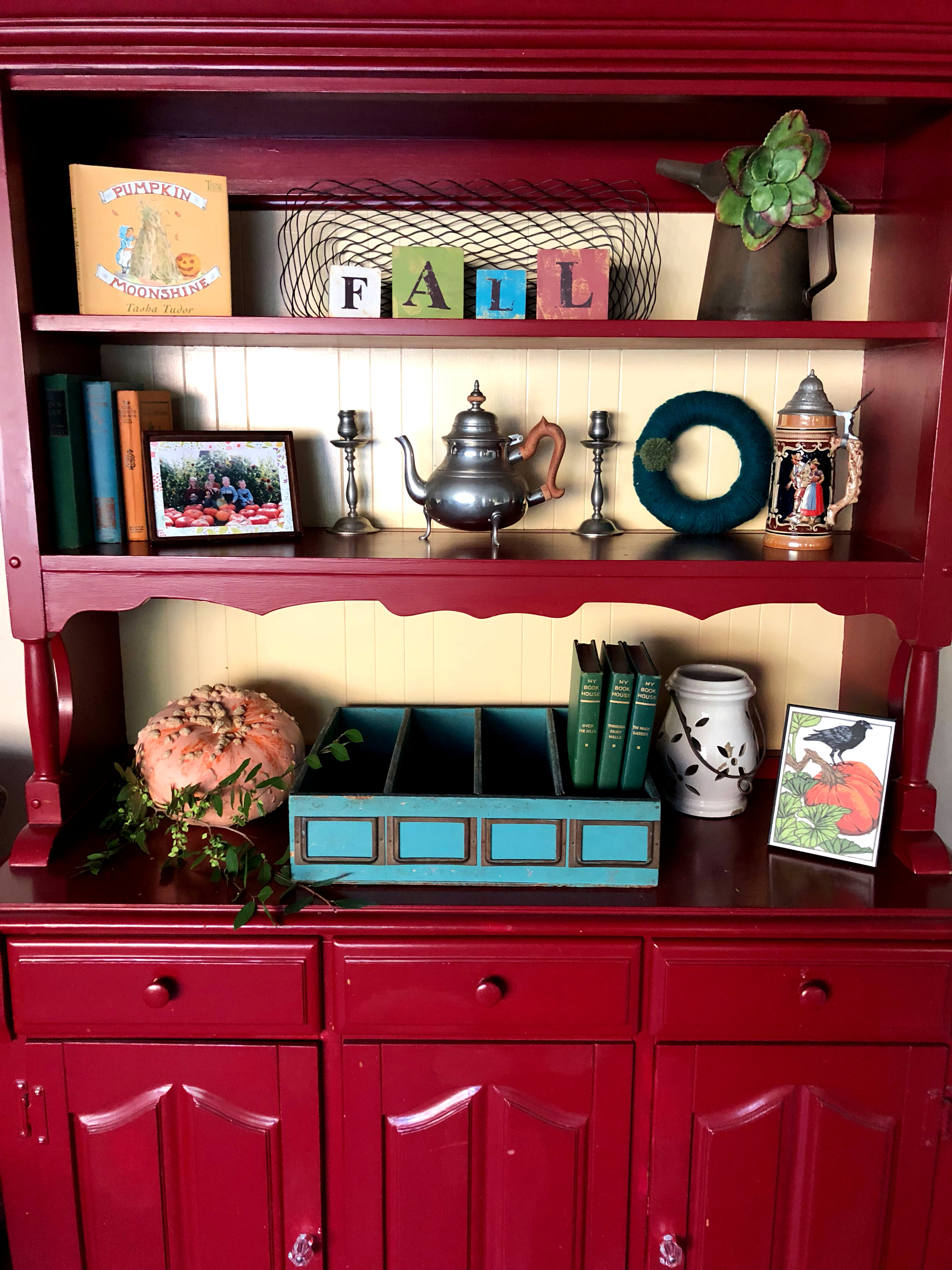 A favorite children's book, pewter pieces from a dear friend, a photo of my children when they were little, old books from a neighbor's yard sale, yarn wreath made by my daughter, an old French drawer, an old oil can, and a card from Trader Joe's taped to a frame.