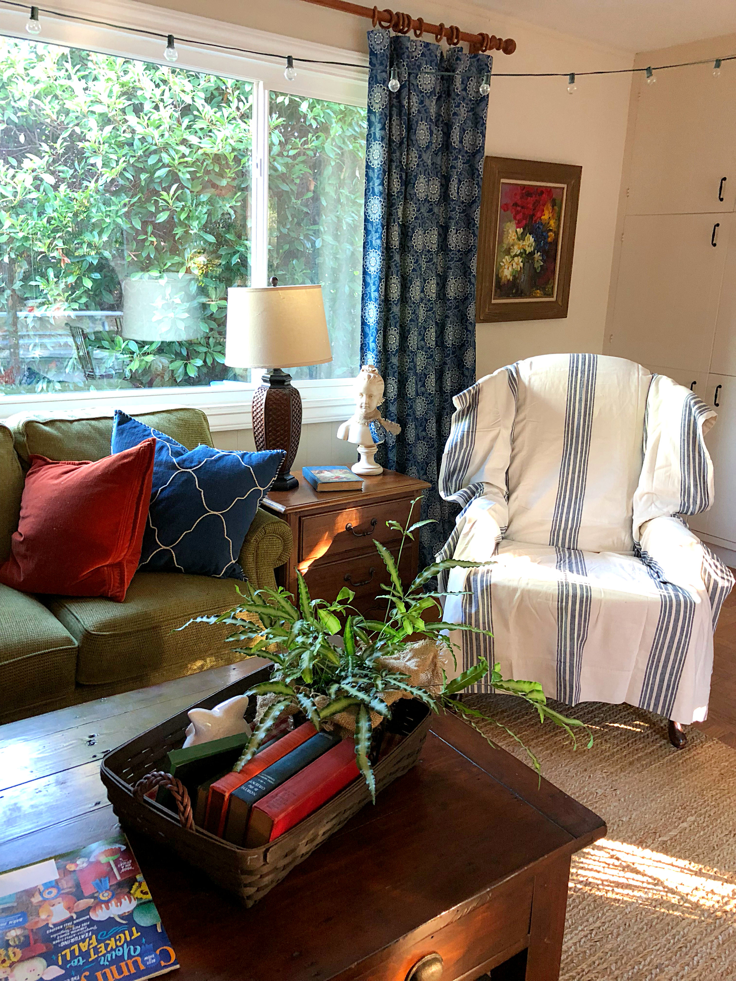 A few touches of Fall color change this room with the season. The striped chair is a roadside find with a PB curtain over it. Curtains - calico corners fabric sewn by a friend, end table, lamp, bust - consignment, oil painting by my grandmother, sofa - Flexsteel, pillows, rug and coffee table - Pottery Barn, string lights because we don't have overhead lighting.
