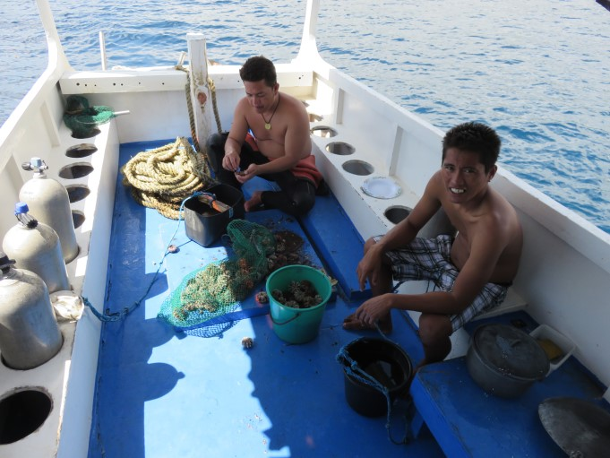 Dandan our guide and a deck hand eating sea urchins