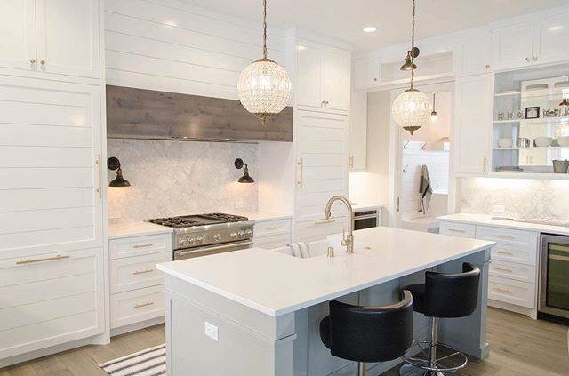 This gorgeous white kitchen design features gold plumbing fixtures, bronze sconces, and leather bar stools. We love how clean and elegant this looks--glam with a touch of rustic! . . . .  #interiordesign #whitekitchen #dreamkitchen #farmhousekitchen #kitchendesign #KitchenLife #kitchendecor #mykitchen #kitchenware #kitchens #inthekitchen #inmykitchen #dreamkitchen #kitchenremodel #kitcheninspo #styling #kitchenideas #instakitchen #modernkitchen #kitchensin #kitchenrenovation #healthykitchen #homestaging #realestate #stagedtosell