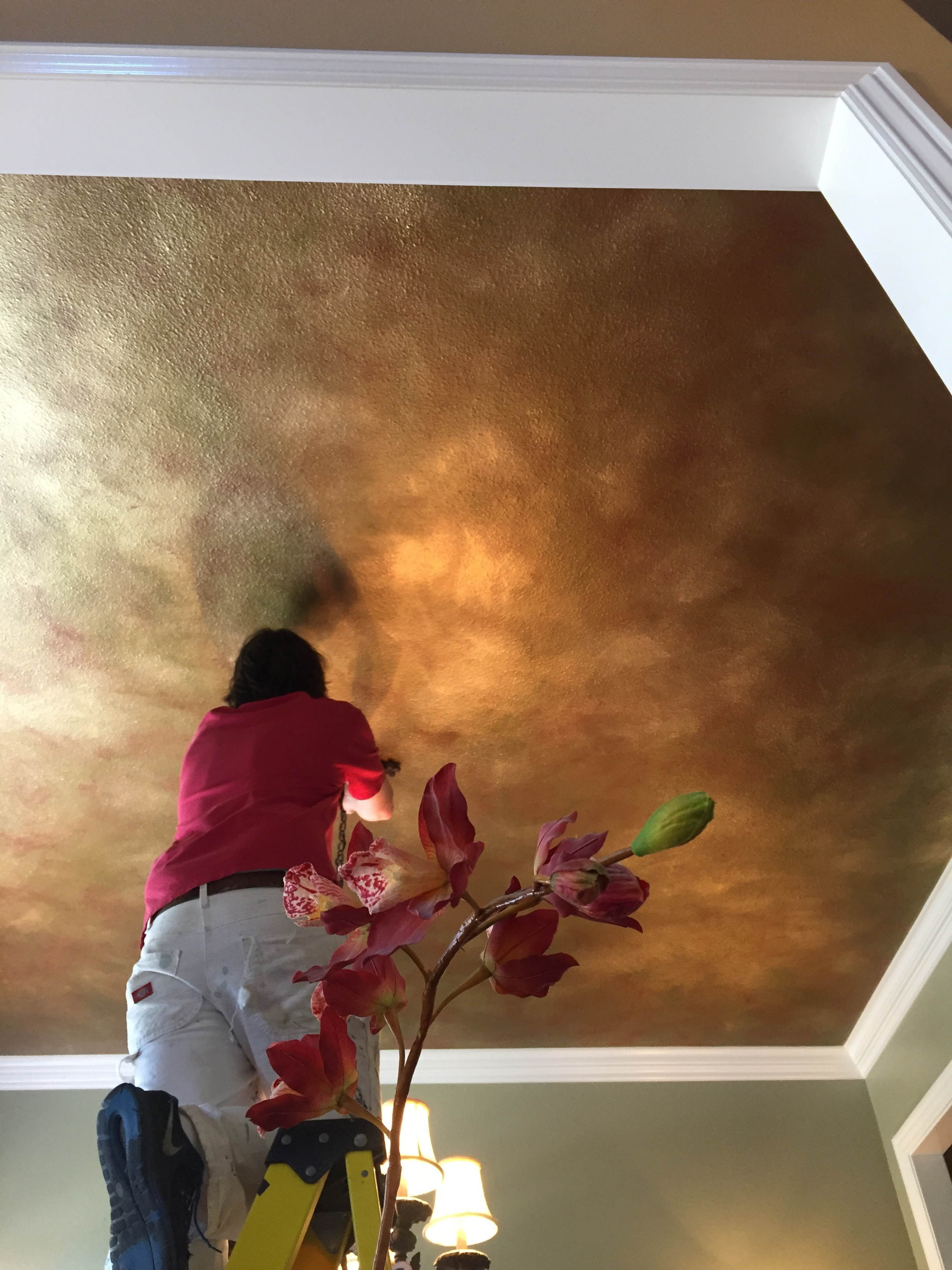 This ceiling incorporates green, red, and gold details from the room