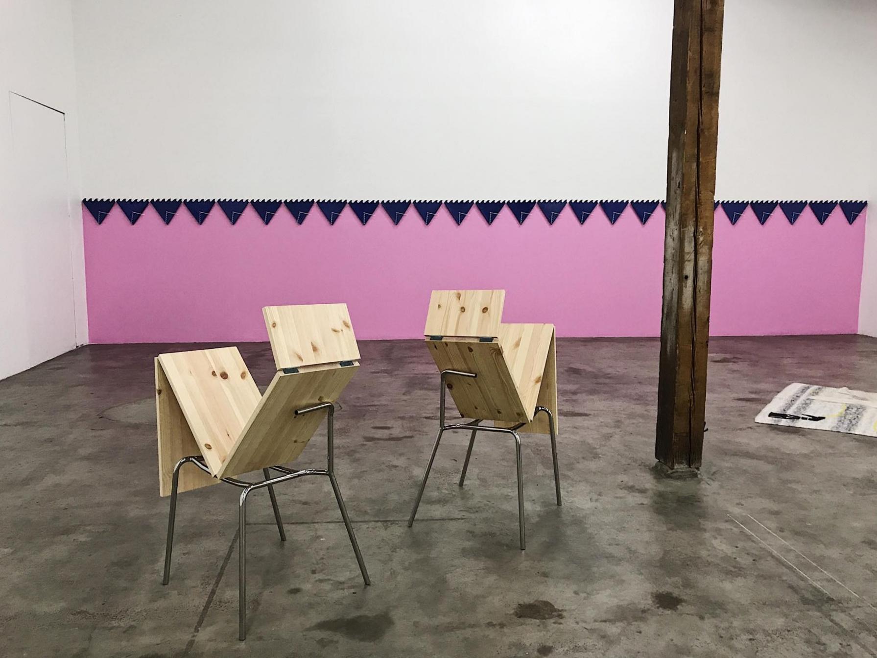 Emily Roysdonin seinämaalaus tuo väriä galleriatilaan. Vinoutuneita tuoleja muistuttava  Idle (2017) on puolestaan Luca Frein käsialaa.