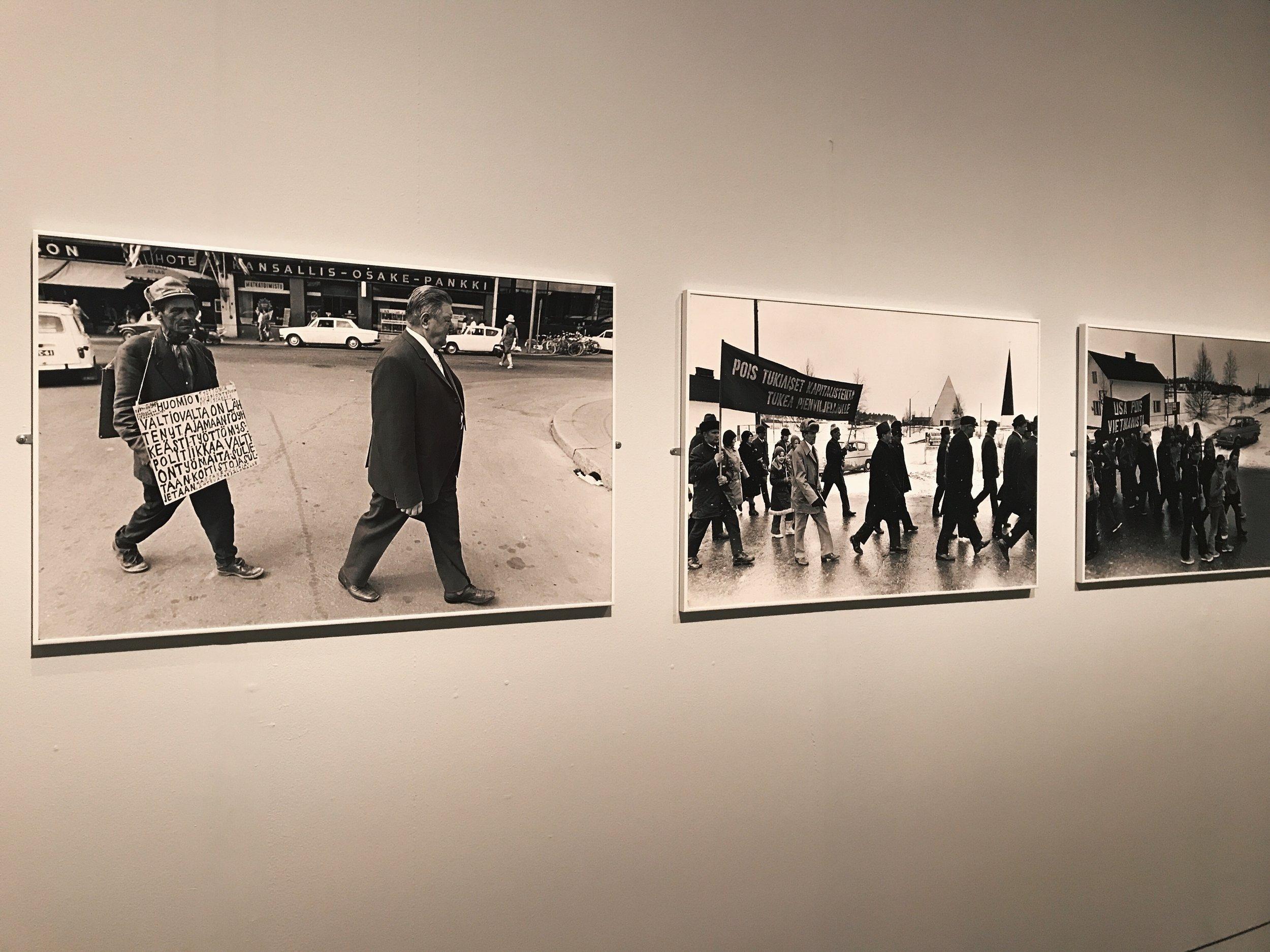 Kalervo Ojutkankaan valokuvat osoittavat, että 1970-luvulla Suomessa marssittiin esimerkksi kapitalismia vastaan. Seuraavalla seinällä Saana Wang tarkastelee puolestaan nykyhetkeä ja suomalaisen yhteiskunnan tulevaisuutta muun muassa Rajat kiinni -mielenosoituksen kautta.