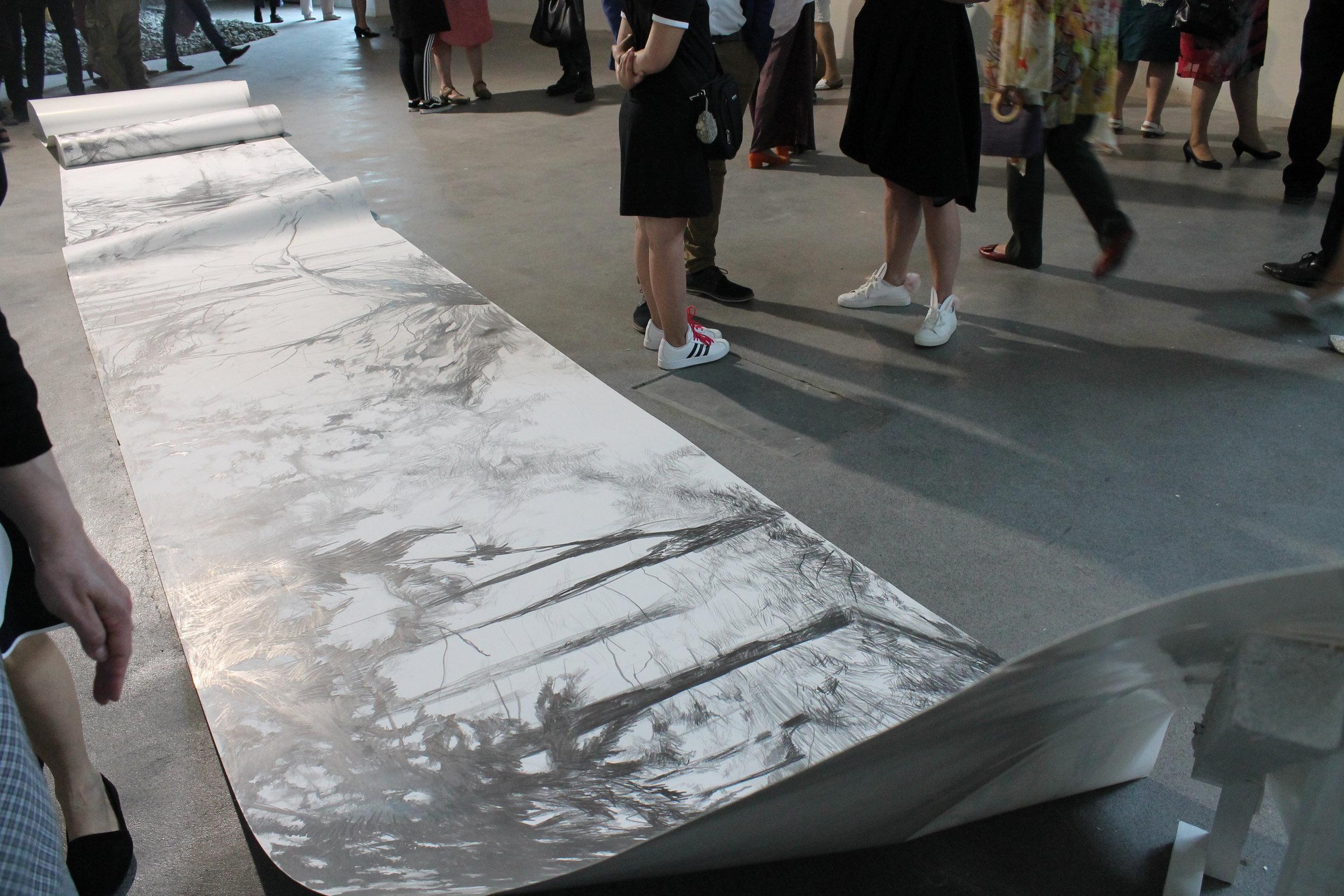 Tiina Kivisen valtava  Onnennotko  -piirustus rullaantuu näyttelytilan halki.