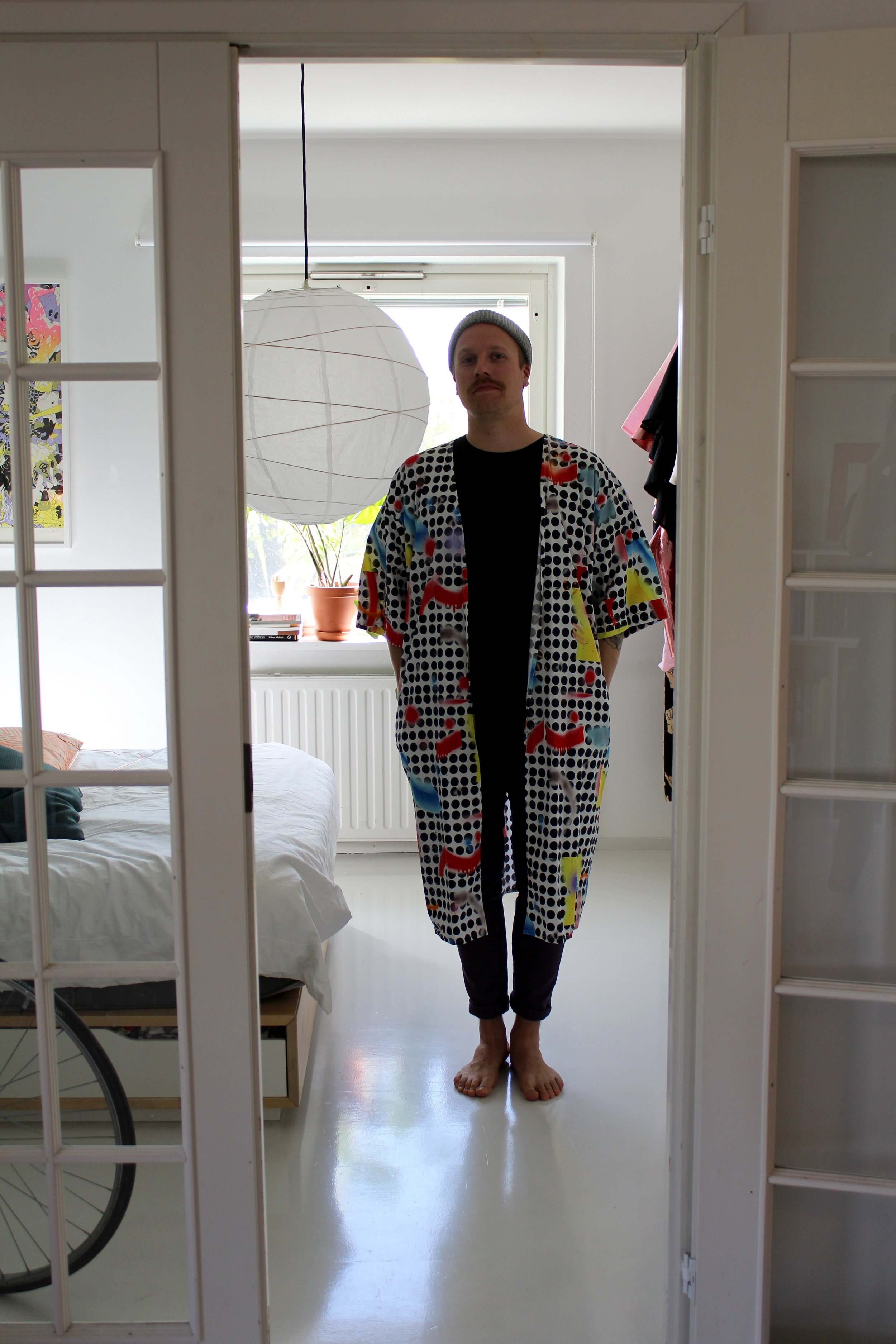 Ahtisen Vimmalle suunnittelemat printit ovat iloisia ja värikkäitä. Kuvassa hänellä on yllään aiemmasta mallistosta tuttu, omalla printillä varustettu paita.