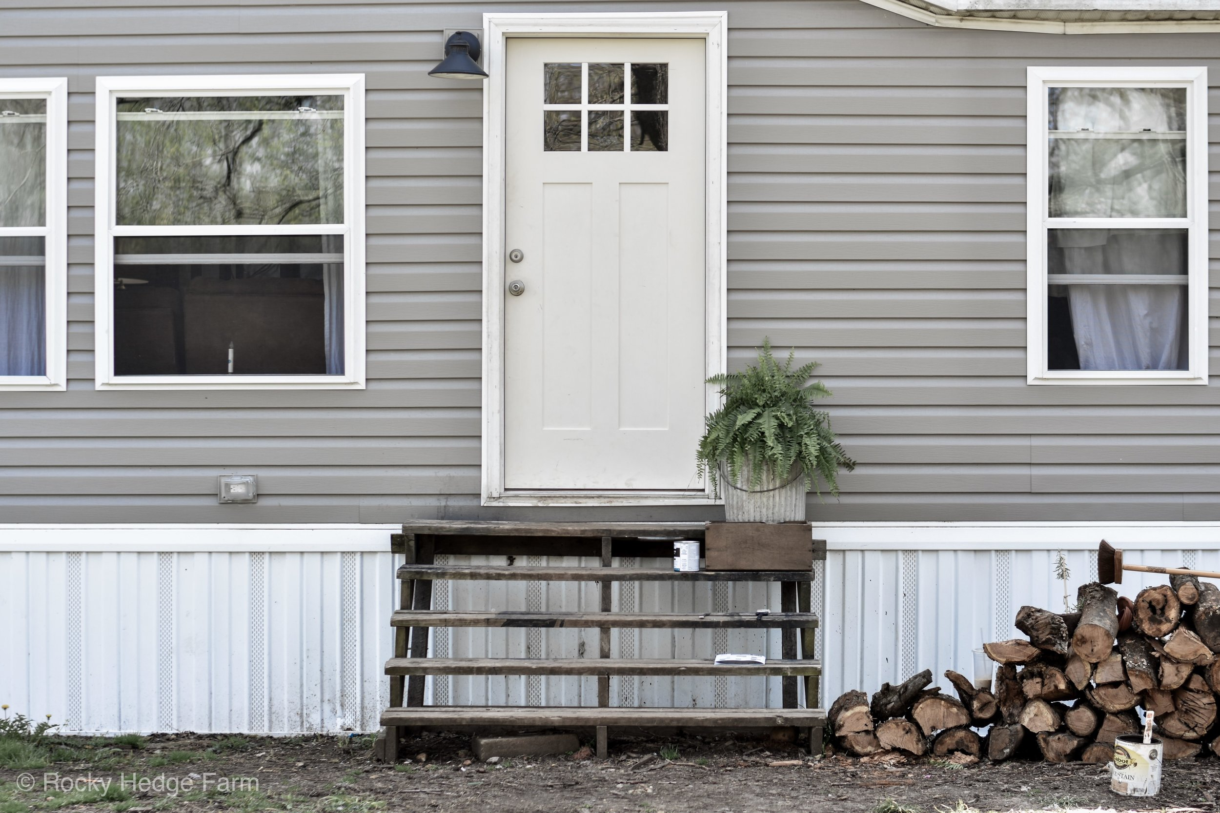 Double Wide Mobile Home with Gray Siding and White Door. Exterior of Mobile Home - Mobile Home Porch Makeover | Rocky Hedge Farm