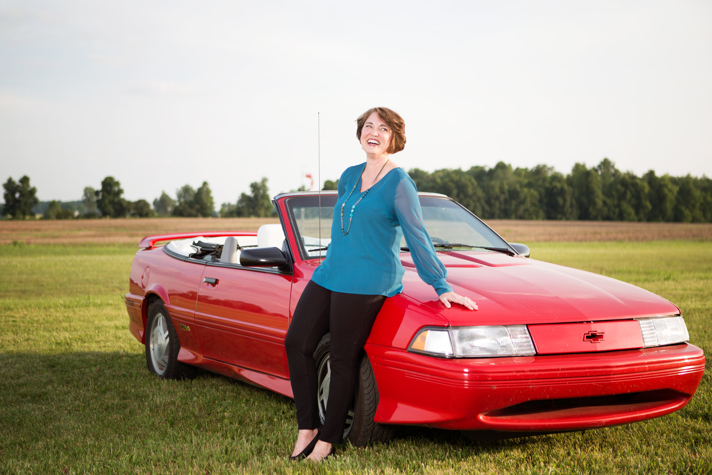 picture of woman leaning against a car
