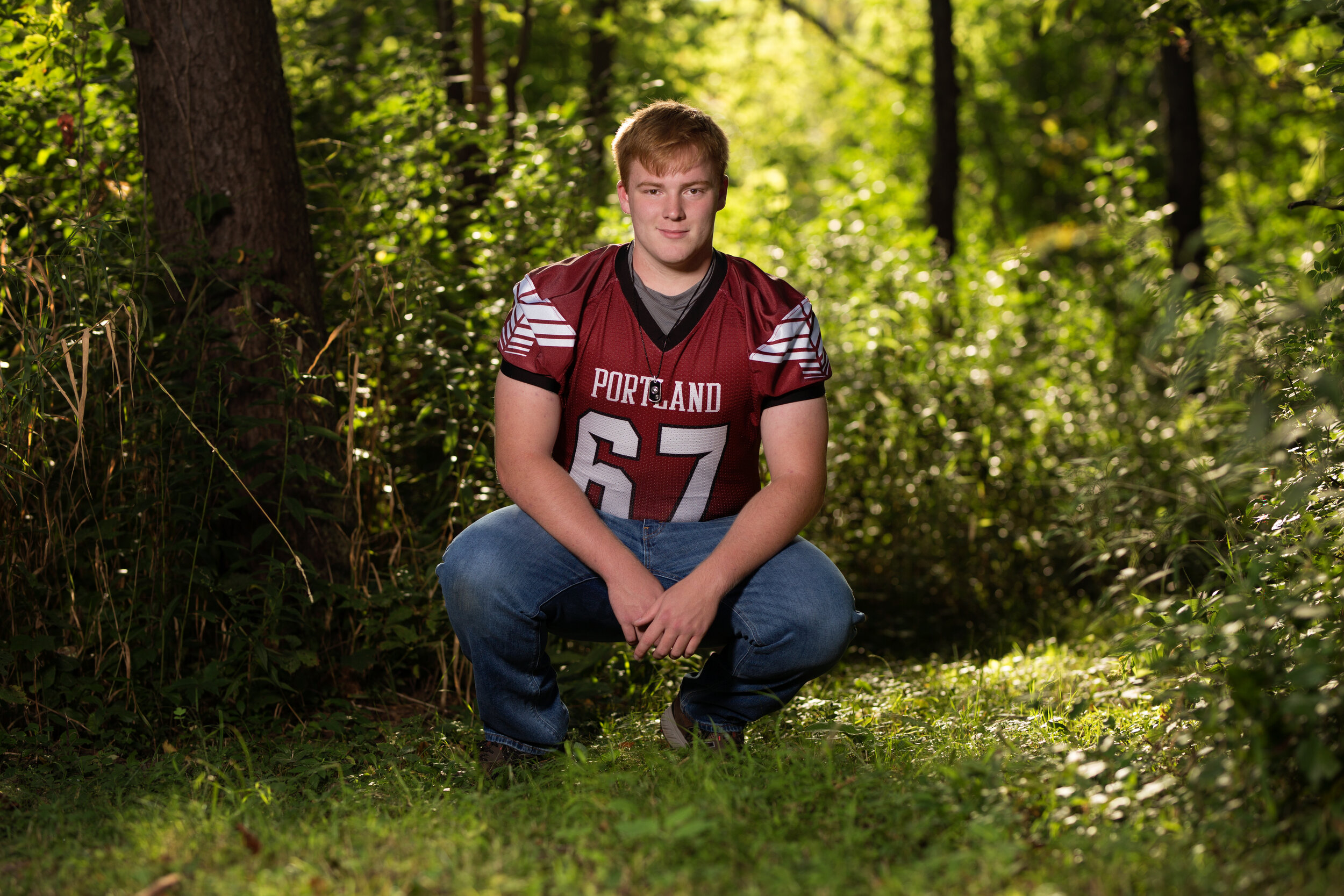 senior picture of boy crouching in football jersey