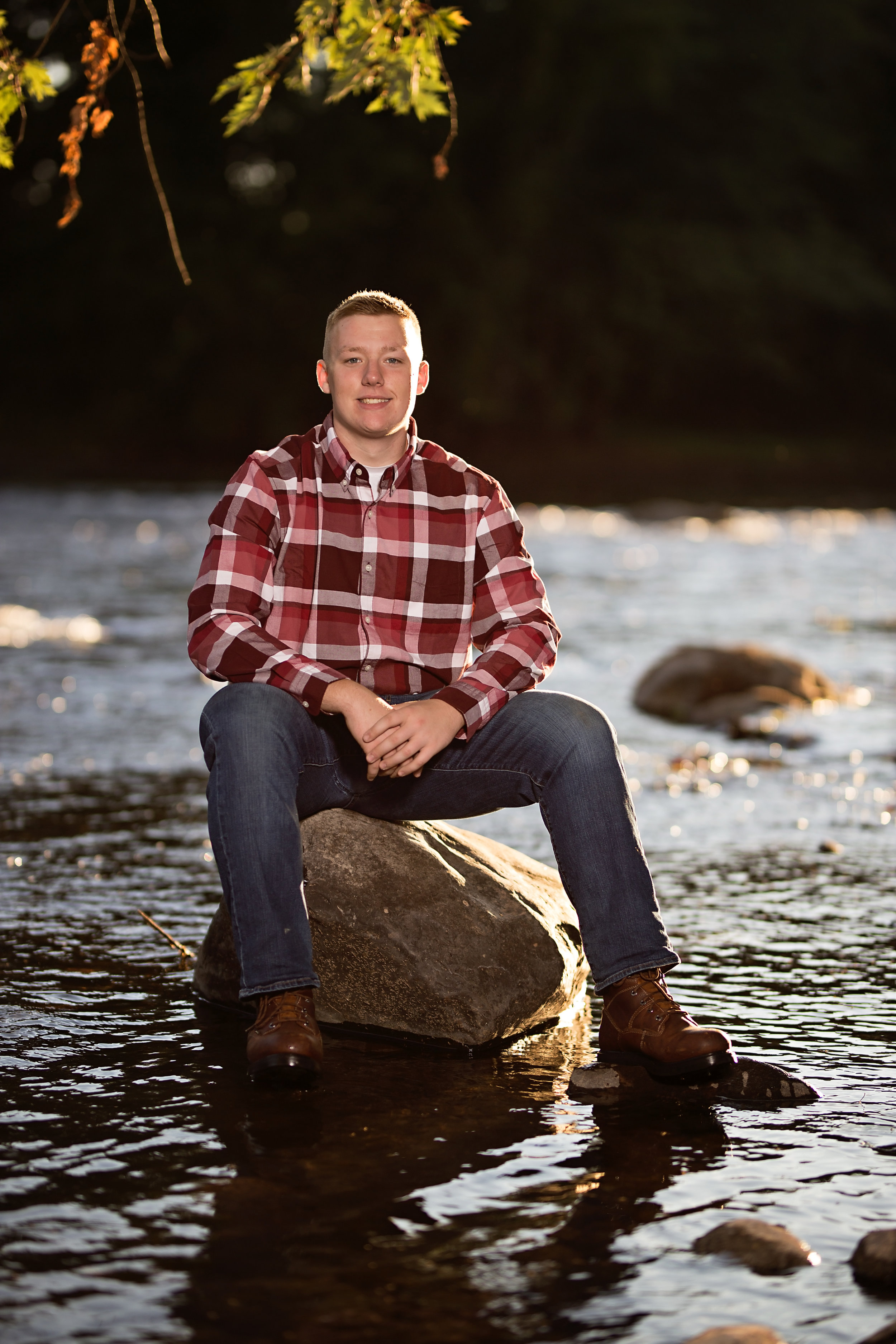 senior portrait of boy sitting on rock in the river