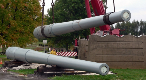 Restoration complete, the first gun is lifted into place