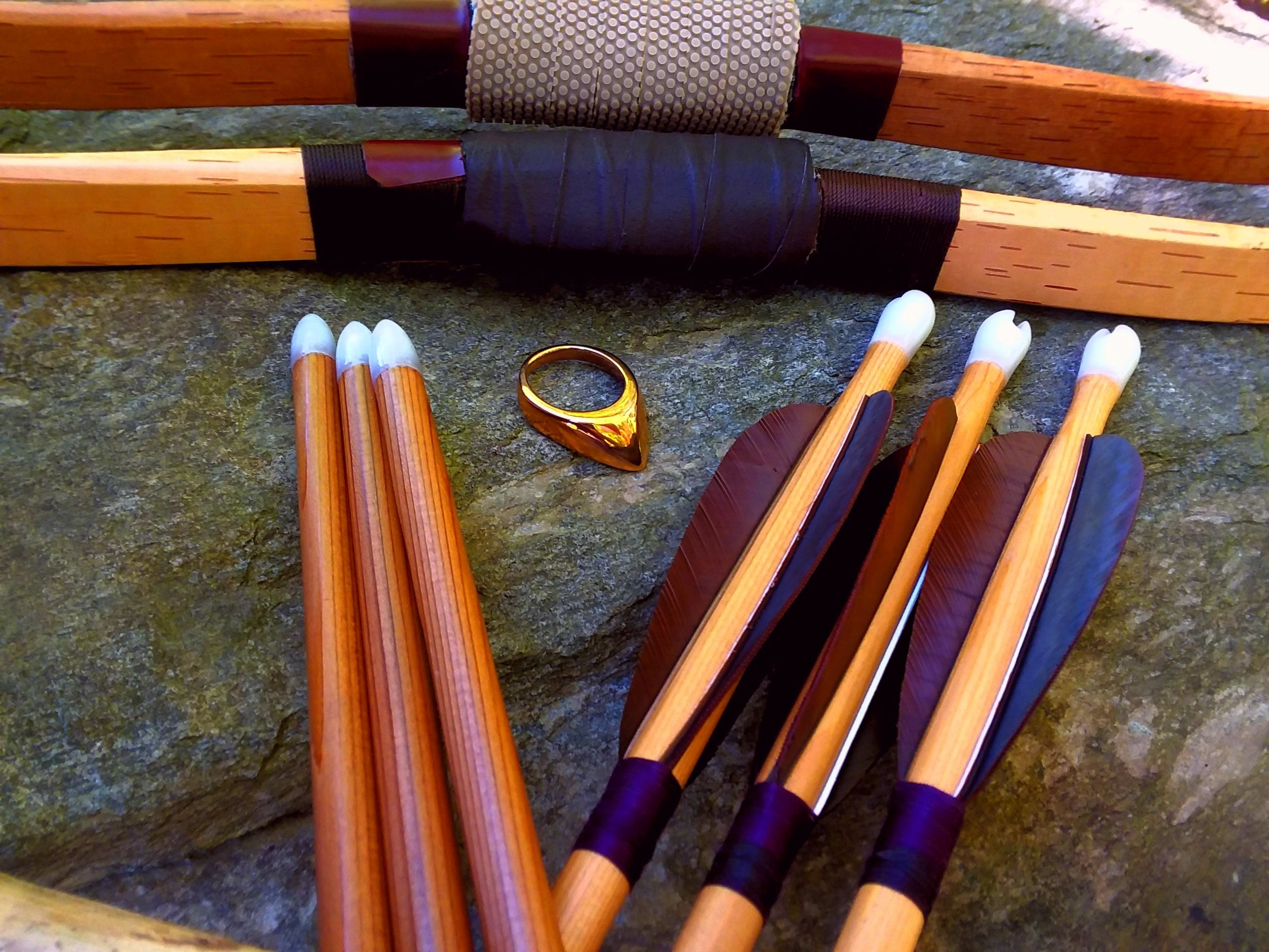All done. Three lighter cedar arrows against three darker ones. Seen here, anachronistically, against two Korean style bows and our Byzantine style ring. The bright outdoor light really makes the ivory points and nocks pop.