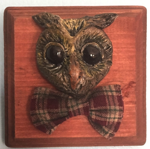 """WHO ME?   This mounted owl head was sculpted out of clay, then painted by hand. His bow tie was sewn out of vintage cloth. The wood panel he is mounted on is 6"""" x 6""""."""