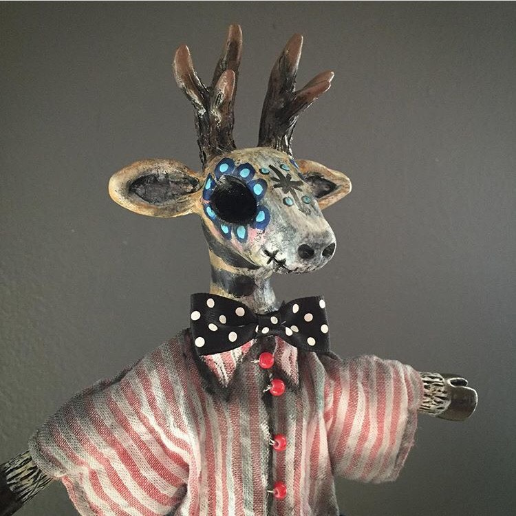 DAY OF THE DEAD DAPPER   This Stag was created in the Day of the Dead style.Cone puppets are set inside decorative cones. The puppeteer can pop the puppet in and out of the cone and swirl to make the puppet dance. The head and hands are sculpted with clay. Body made with wire so the arms can move. Costume hand sewn using vintage and new fabric.