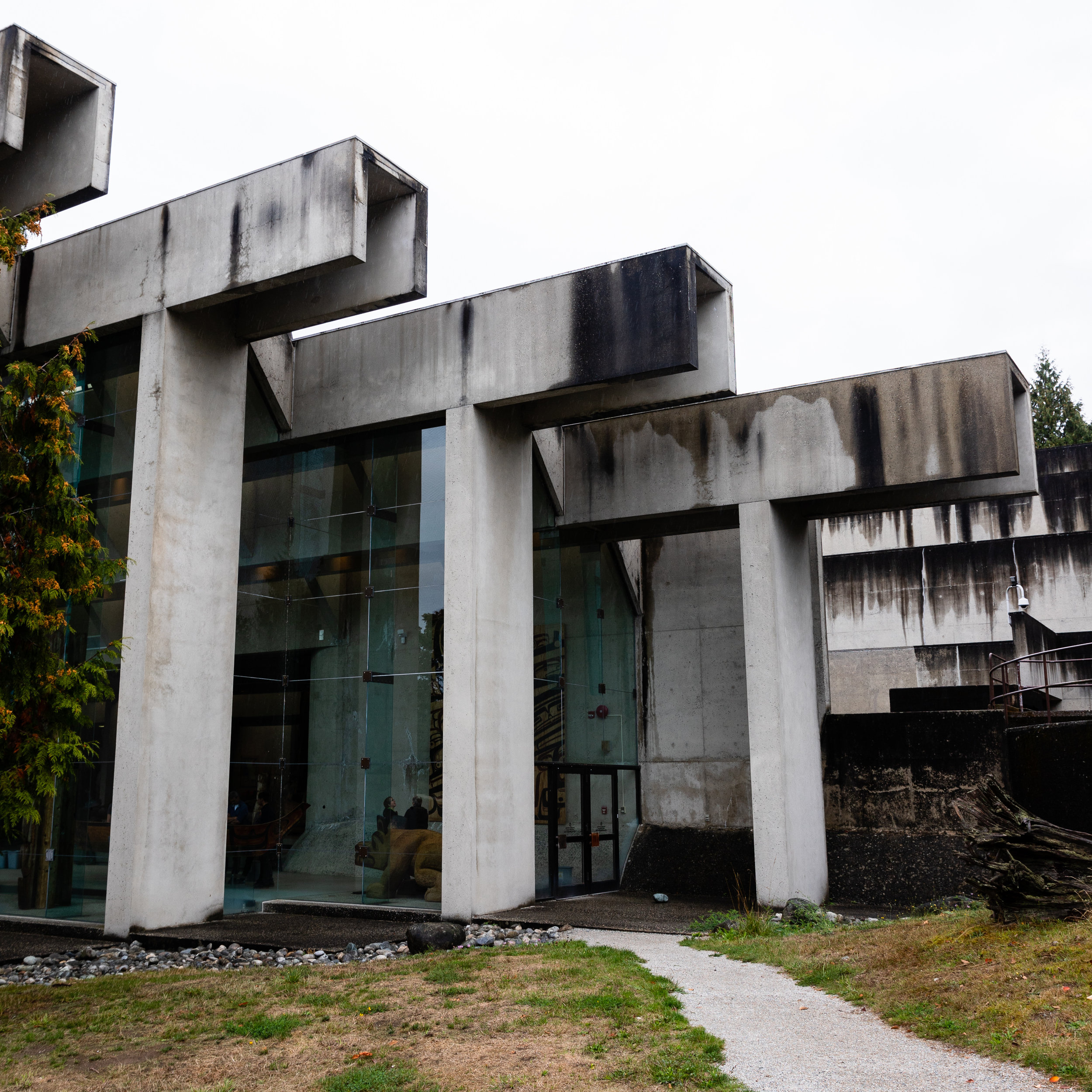 This is the Museum of Anthropology in Vancouver, BC. The shapes of the concrete frame of the museum are designed to reference the traditional architecture of the first peoples, on who's land the museum is built. On a rainy day like the day this photo was taken the textures in the concrete come to life.