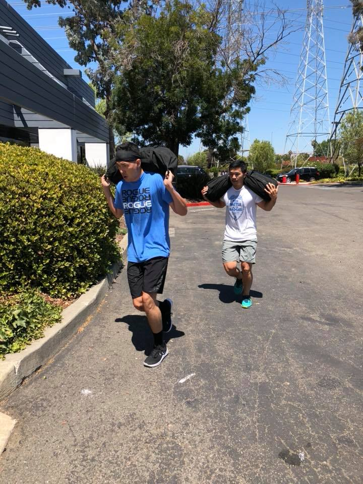 Junsan and Cary moving that sandbag with ease