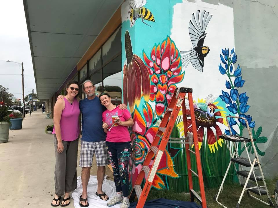 "Finishing up my first group/outdoor mural with friends. L - R: Bejat, Ronnie, and Jody (me). Completed November 2017 in downtown San Marcos, TX. Near LBJ and MLK. The big ""Indian Paintbrushes"" in oranges, pinks, and dark teal are my contribution. I had so much fun painting this with everyone!"