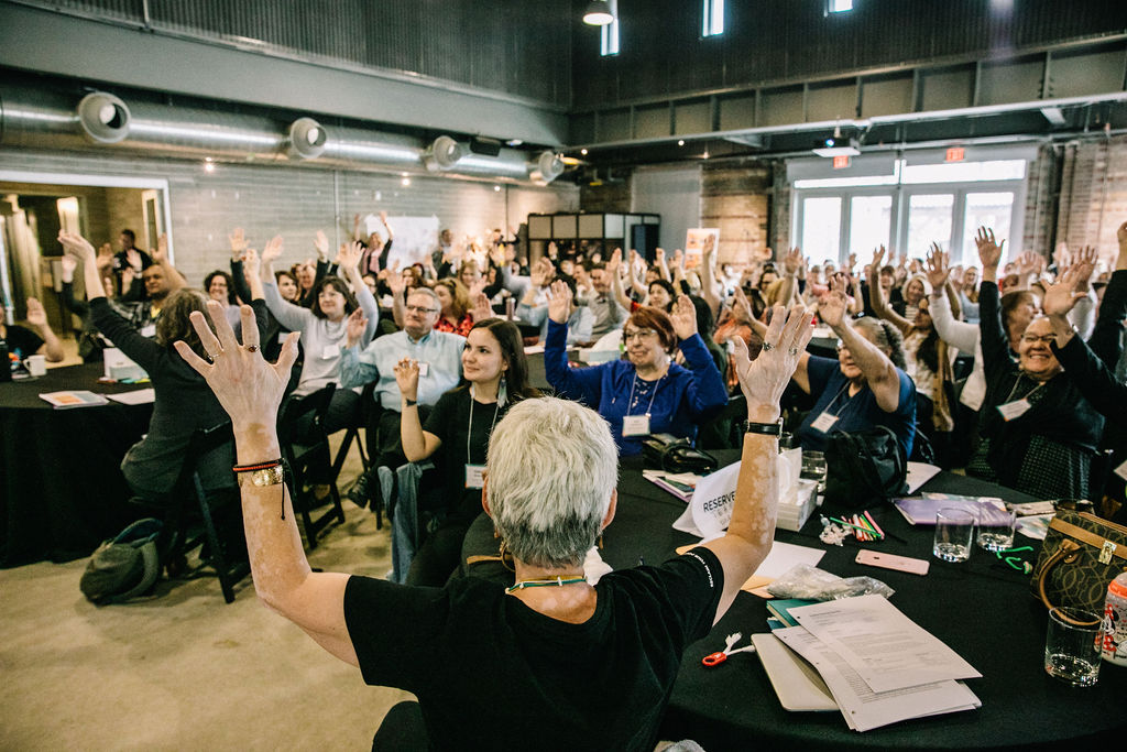 Food for Health Symposium attendees raise their arms to indicate connecting personal values to organizational values around food.