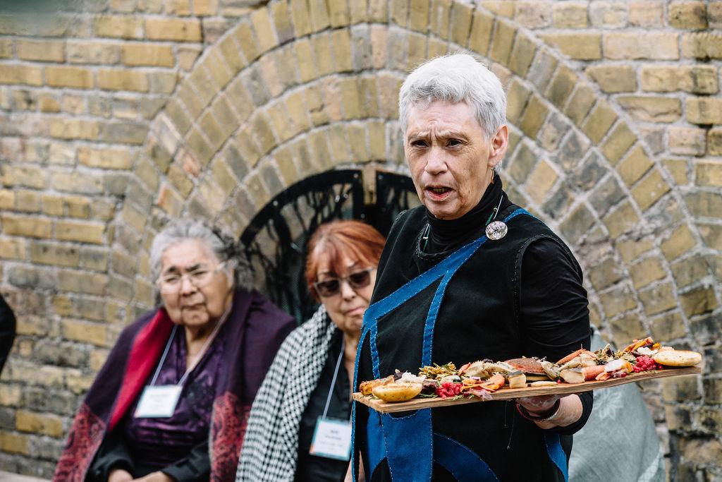 La gardienne du savoir haïda Sue Gladstone offre une assiette aux ancêtres en compagnie de l'aînée haïda Margaret Edgars (à gauche) et de l'aînée métis May Henderson.