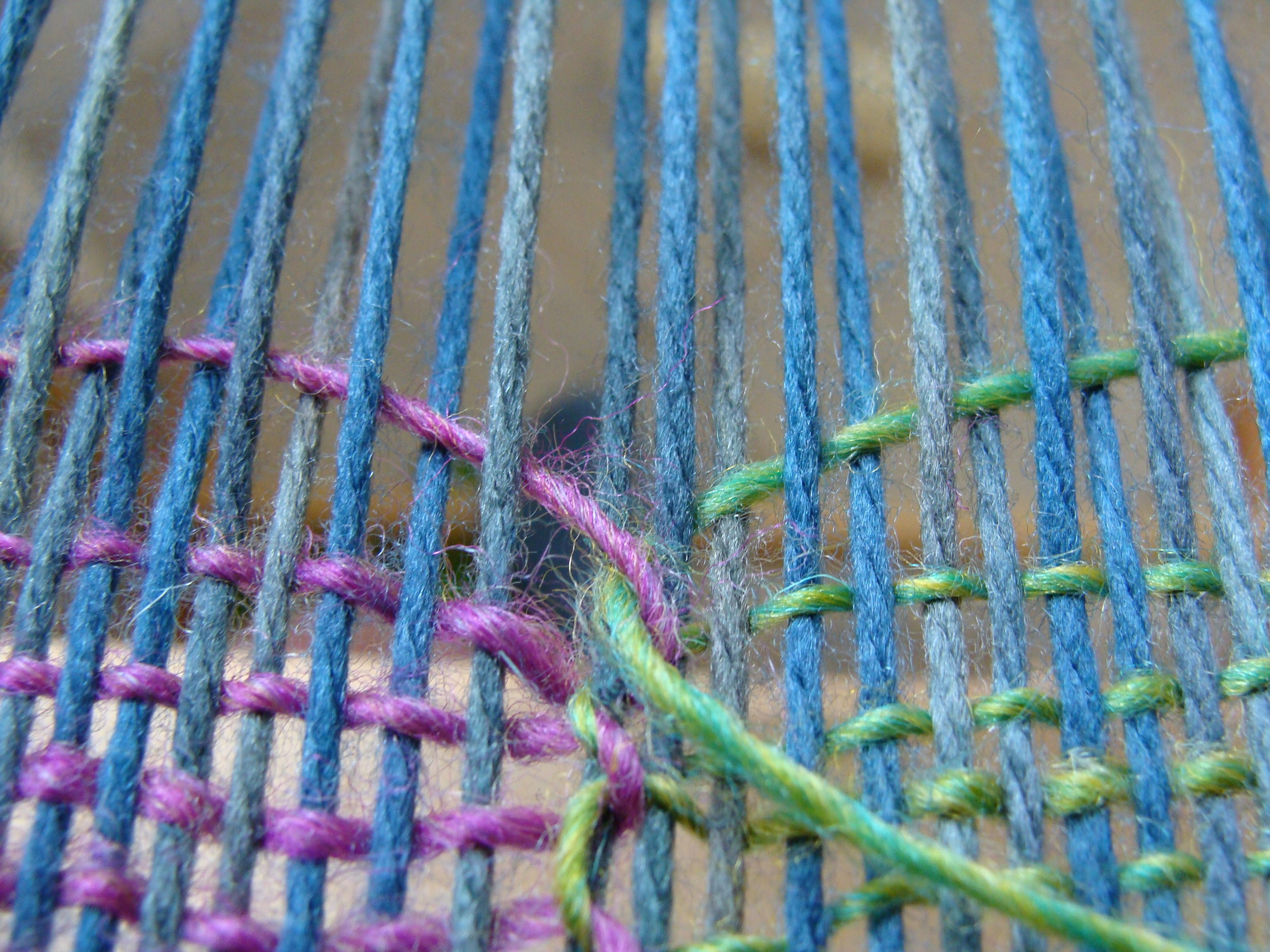 Butterfly #2 (pink) interlocks with butterfly #1 (green) and exits out the row at the selvedge.