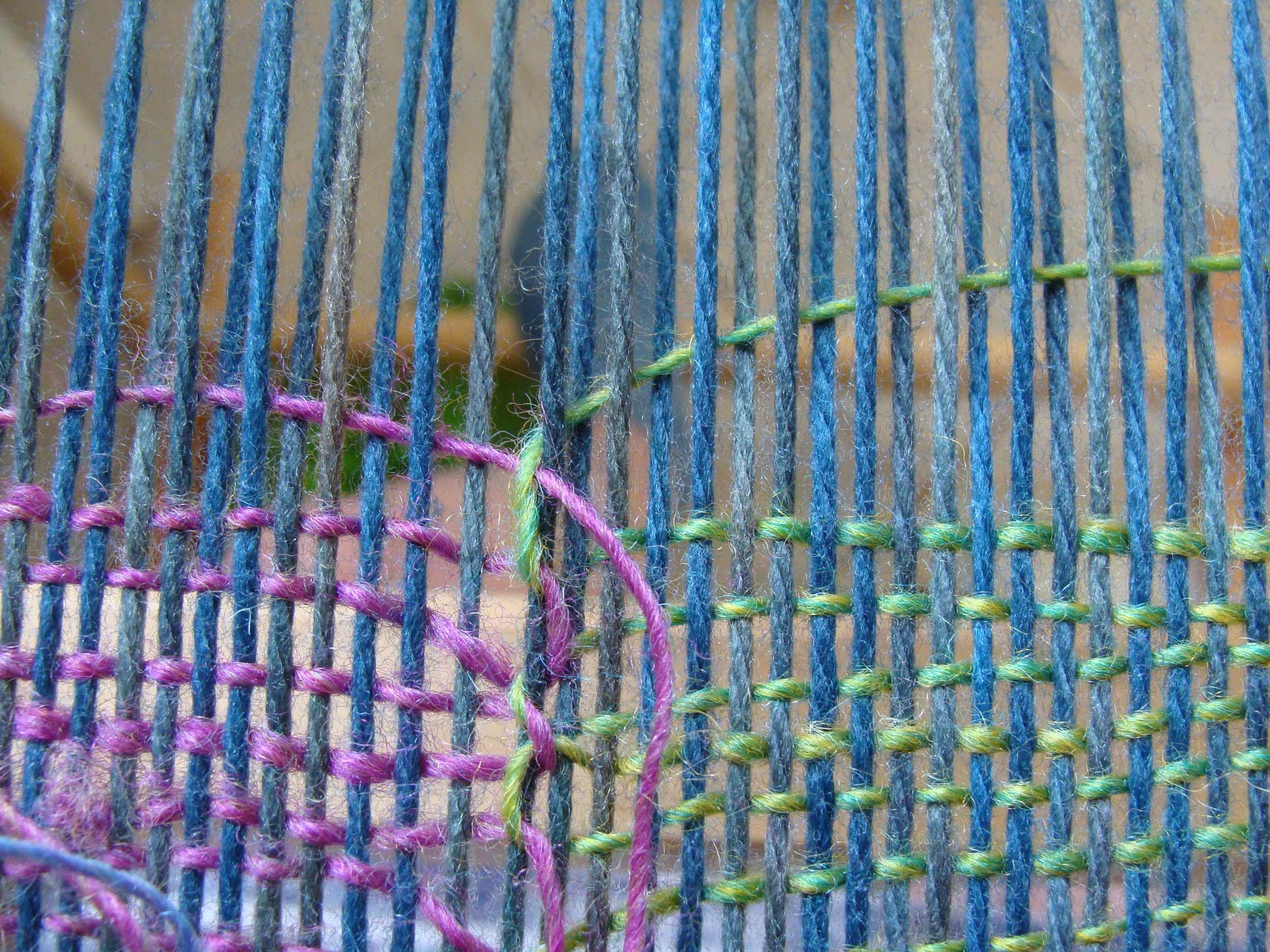 Butterfly #1 (green) interlocks with butterfly #2 (pink) and exits out the row at the opposite selvedge.