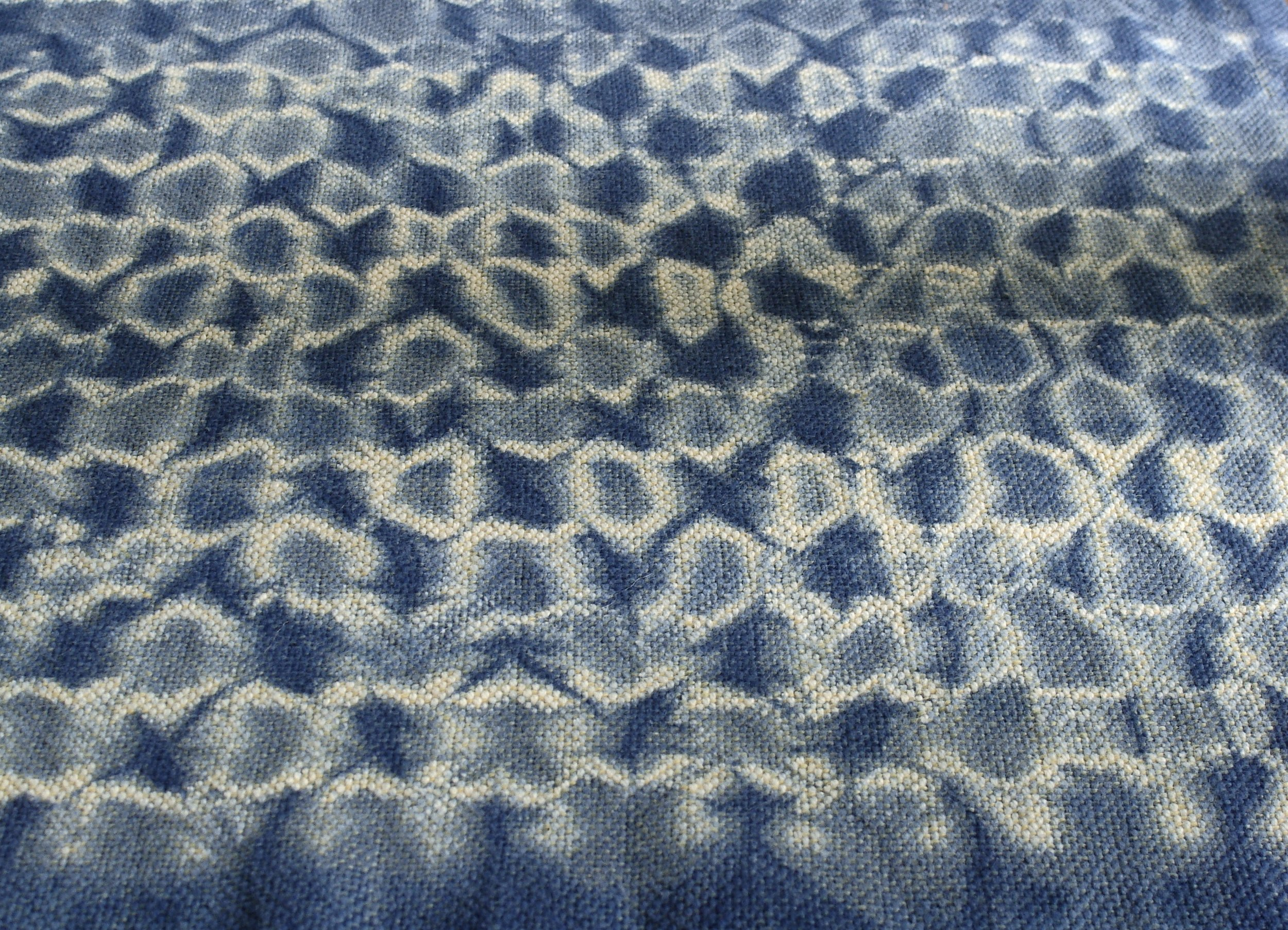 close up of woven shibori table runner dyed with indigo