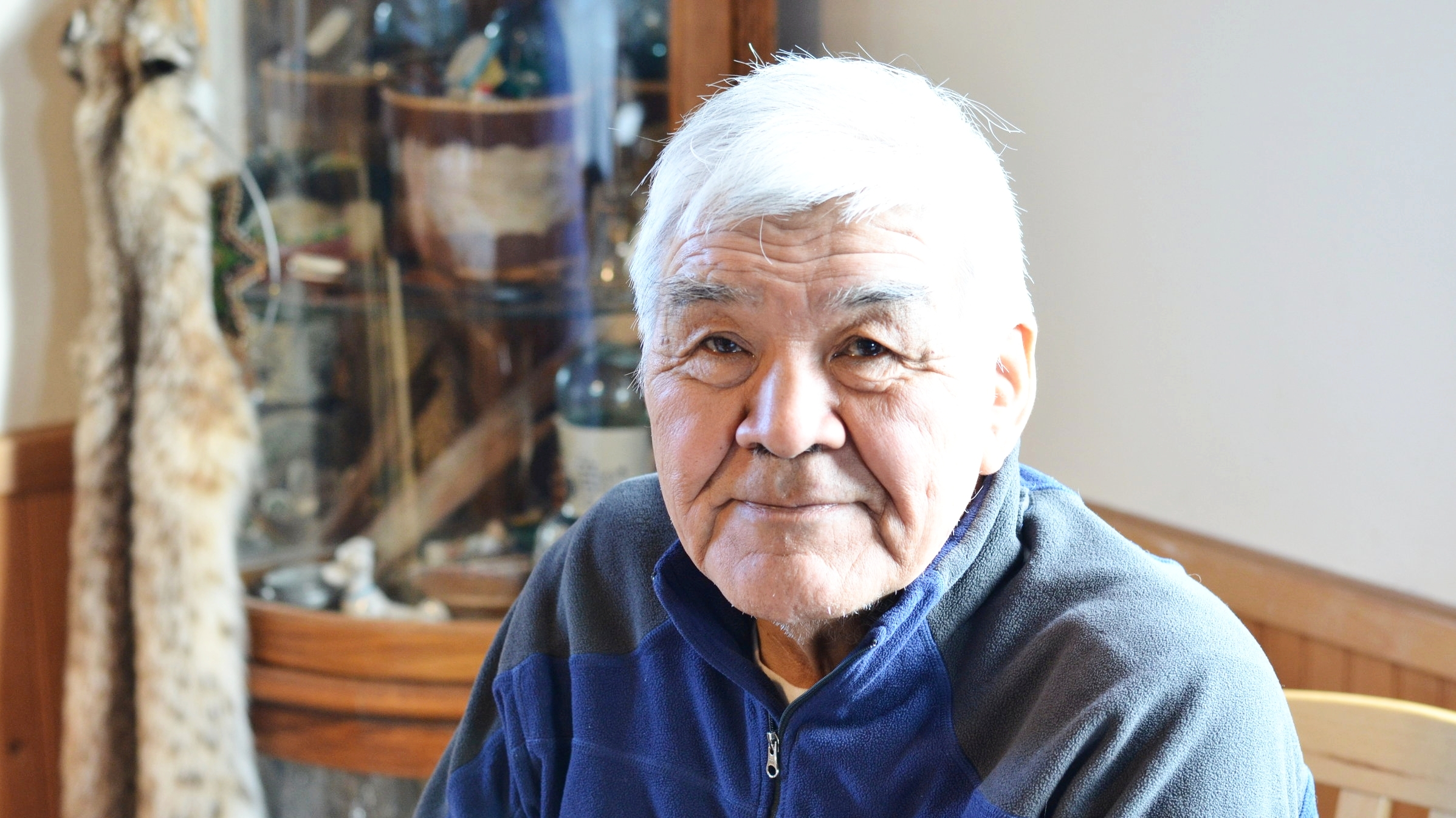 Towarak at the home of his sister, Willa Eckenweiler, in Unalakleet, in front of a case of Inupiaq carvings and art pieces.