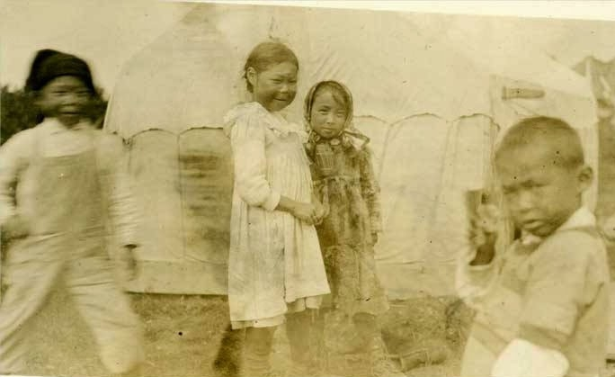 """""""View of four children, two boys and two girls, in front of a tent at Naknek, Alaska."""" Caption also reads: """"Children orphaned by the flu epidemic at Pawik."""" Pawik is a variant name for the village of Naknek. UAA-hmc-0186-volume7-6462, from """"Indigenous Alaska and The Great Influenza Pandemic"""" http://alaskanativestudies.blogspot.com/2014/02/indigenous-alaska-and-great-influenza.html"""