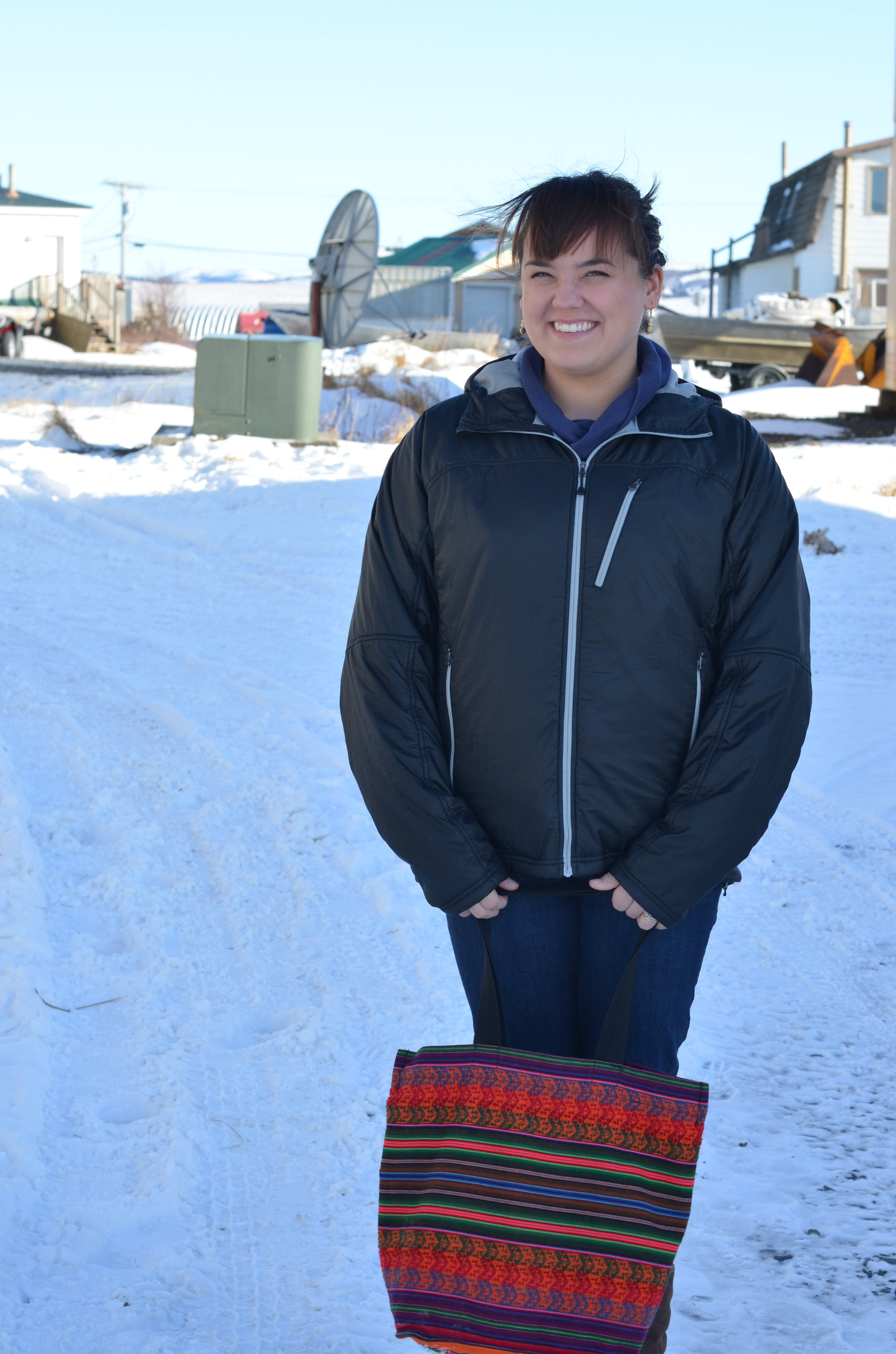 Simonsson stands between rows of houses in Unalakleet.