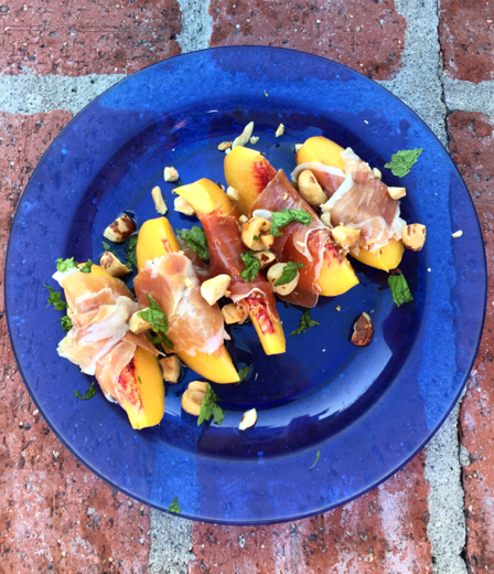 Peaches wrapped in prosciutto, topped with hazelnuts, mint and olive oil.