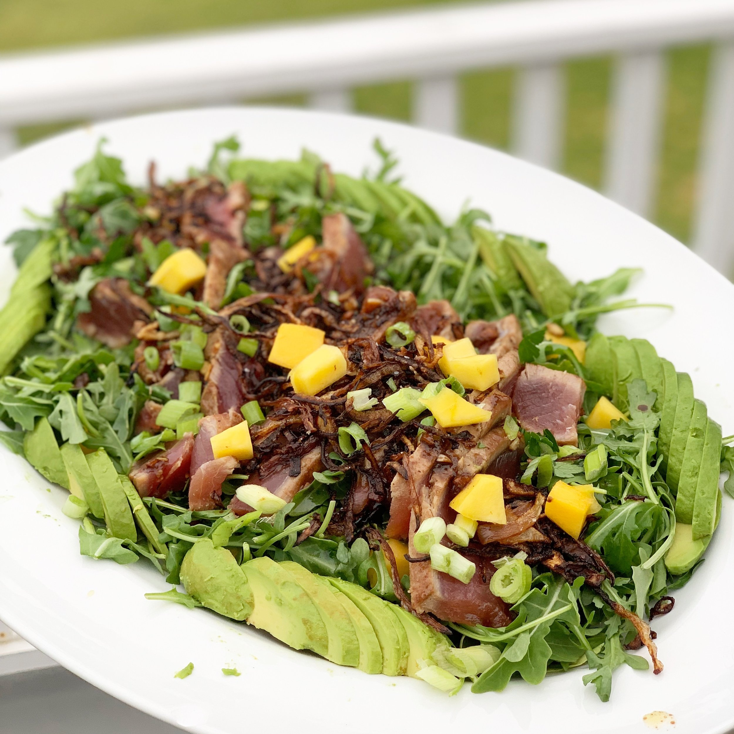 Seared Ahi with arugula, crispy onions, mango, avocado, and scallions with pan drippings for dressing