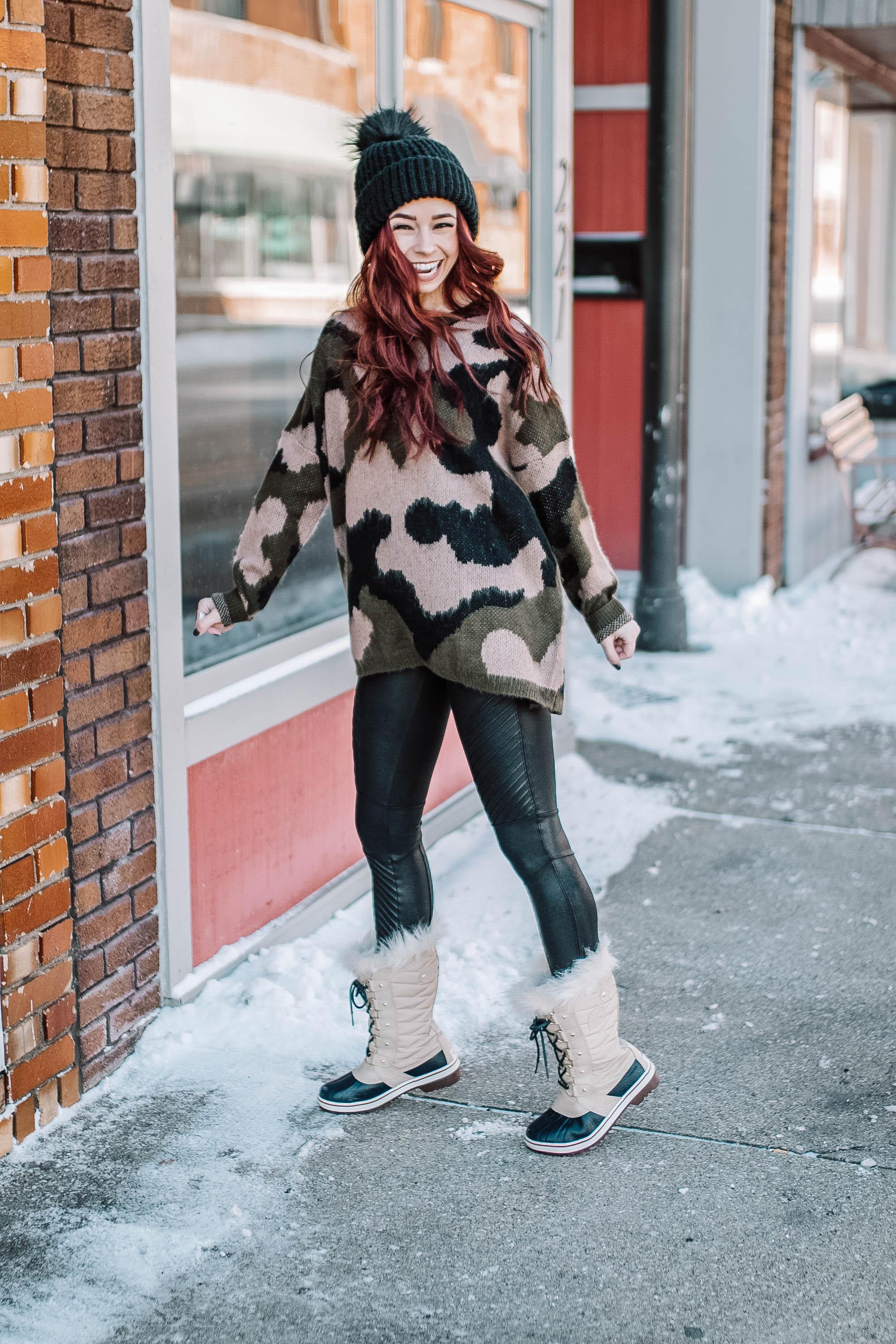 Cute winter trends featured by top US fashion blog, Trendy in Indy: image of a women wearing a Joelle+Co came pullover, Evereve skinny jeans, Sorel waterproof faux fur boots, SPANX faux leather leggings, TOPSHOP pom pom beanie