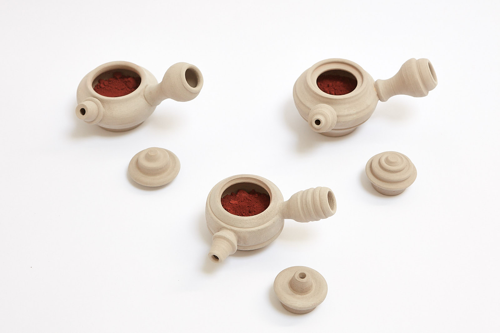 Hibakusha, 2016, 6.5 x 33 x 33, Unfired clay teapots with oxide powder.