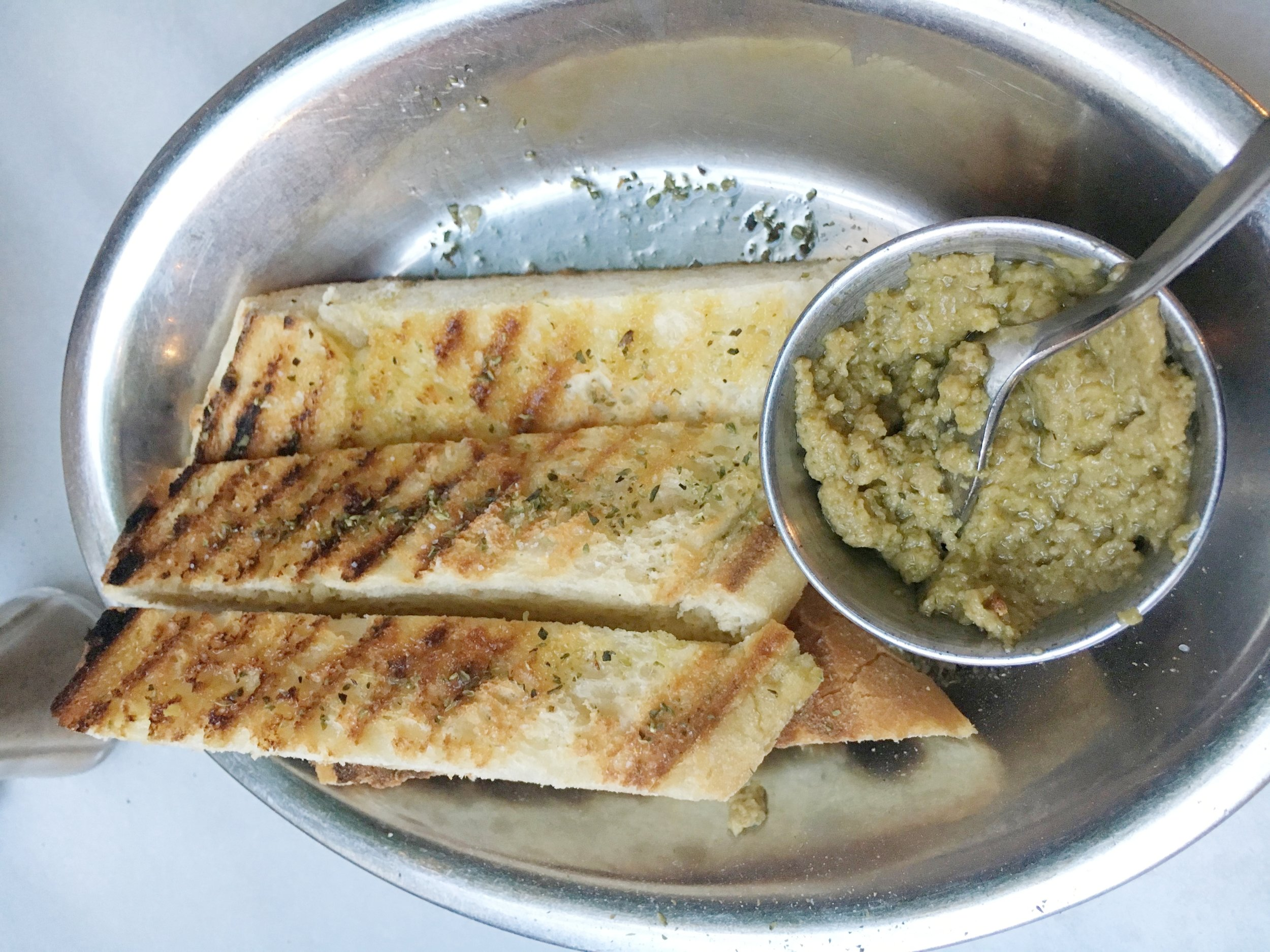 The olive tampanade with olive oil drizzled on the bread.