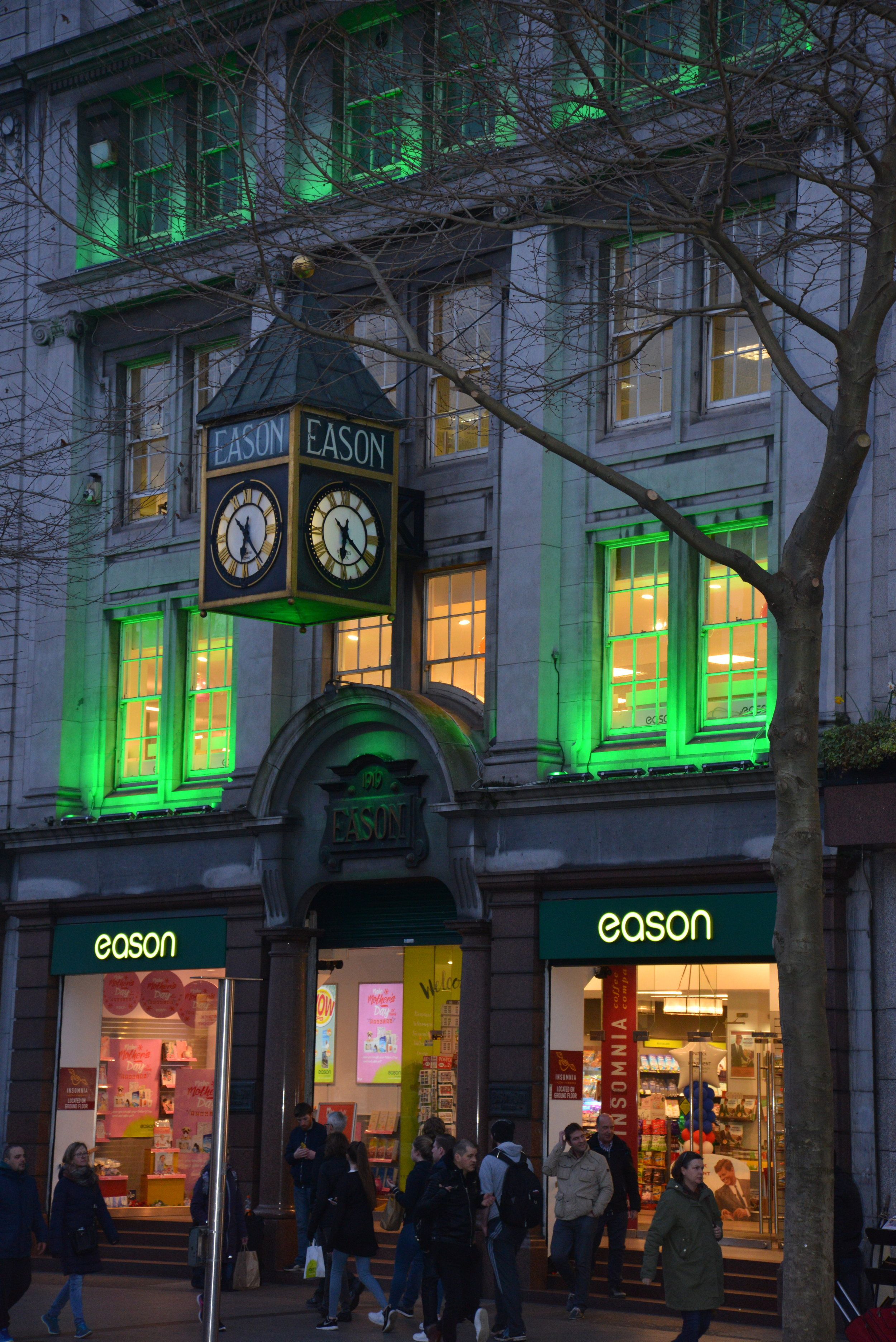 A downtown building lit up green