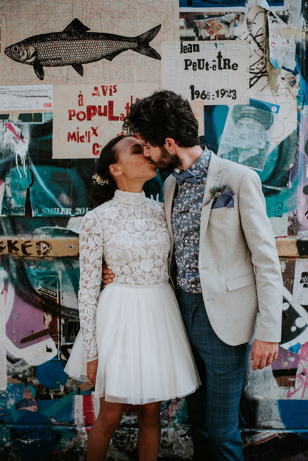 Bride and Groom portrait of a kiss in front of a blue, white, black and purple graffiti wall. These two had an intimate wedding celebration in Shoreditch, London.